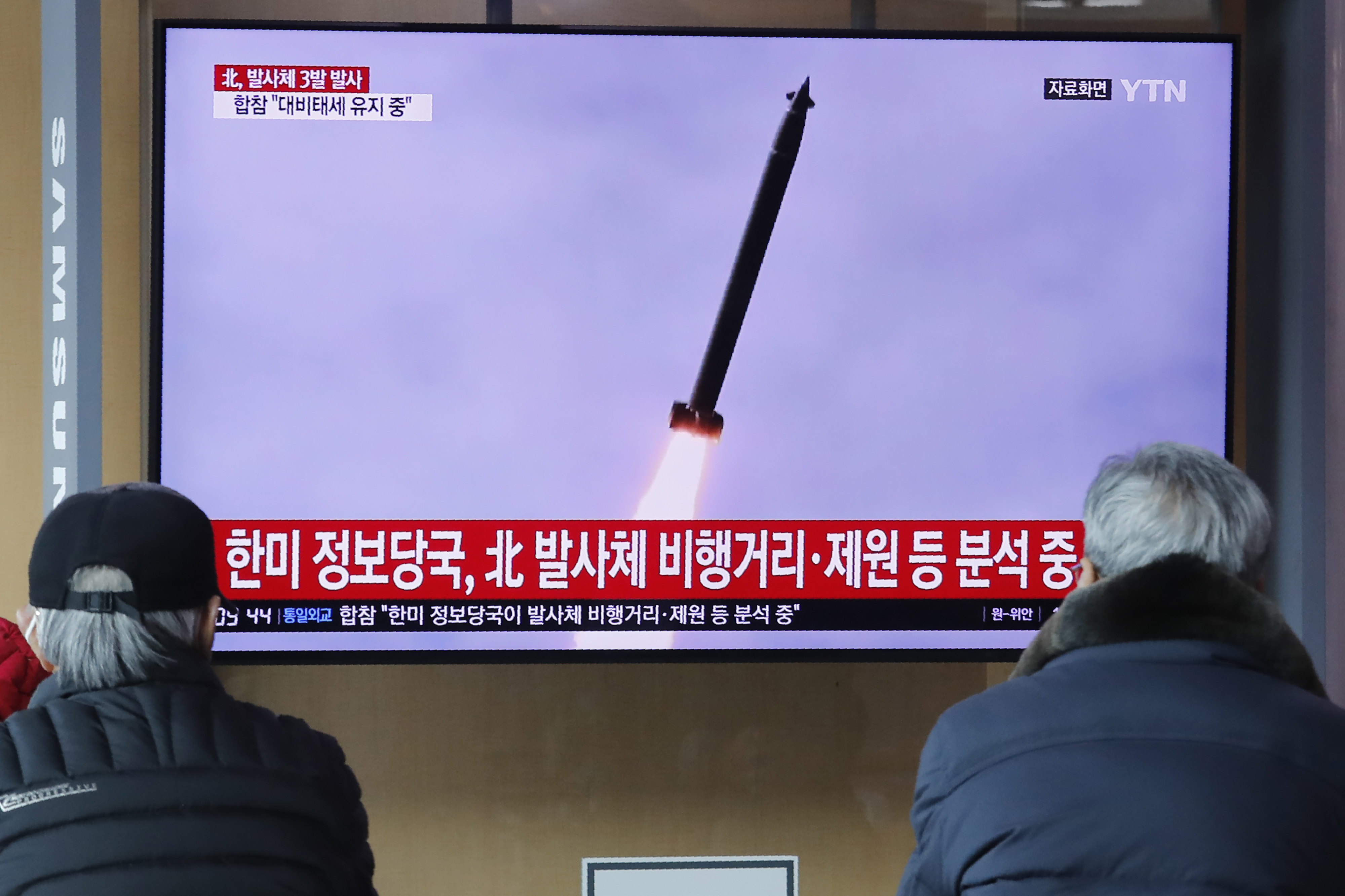 People watch a TV showing a file image of an unspecified North Korean missile launch during a news program at the Seoul Railway Station in Seoul, South Korea, Monday, March 9, 2020. North Korea fired three unidentified projectiles off its east coast on Monday, South Korea's military said, two days after the North threatened to take  momentous  action to protest outside condemnation over its earlier live-fire exercises. The Korean letters read::  South Korea and U.S. intelligence agency analyze North Korea's projectile.