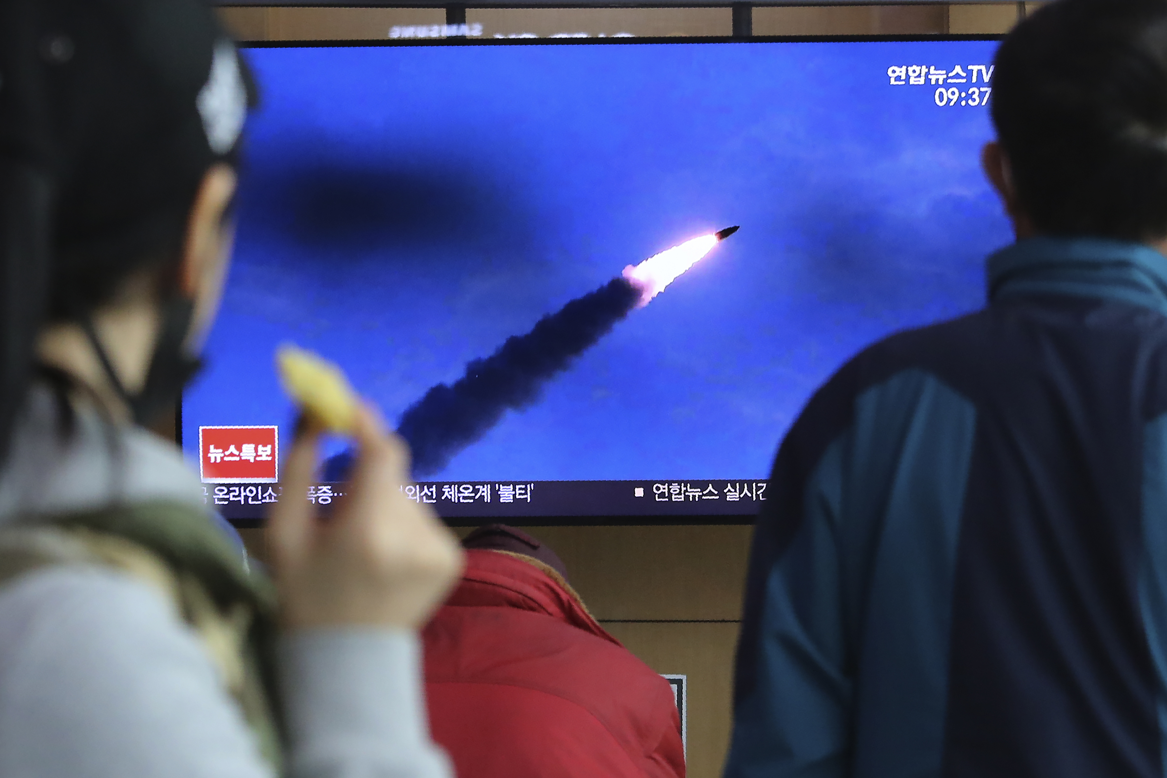 People watches a televsion screen showing a file image of North Korea's missile launch during a news program at the Seoul Railway Station in Seoul, South Korea on March 21, 2020.