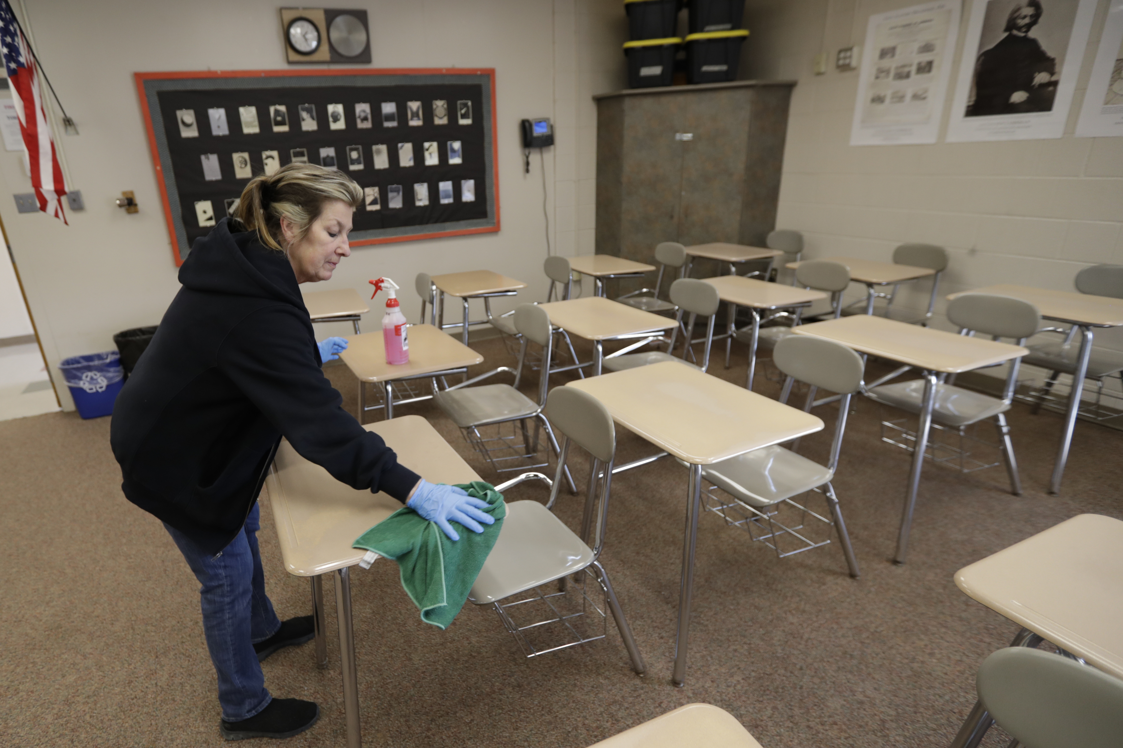 Custodian Patti Alesci cleans desks at Orange High School, Monday, March 16, 2020, in Pepper Pike, Ohio. A mandatory three-week closure of schools to stem the spread of the coronavirus began Monday, bars and restaurants were closed indefinitely, and the state continued preparations for Election Day Tuesday.