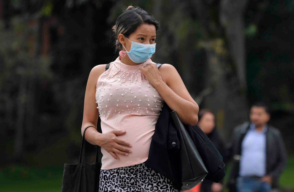 A pregnant woman wears a face mask as a preventative measure against the spread of the new coronavirus, COVID-19, as she waits for the bus in Bogota, on March 16, 2020.