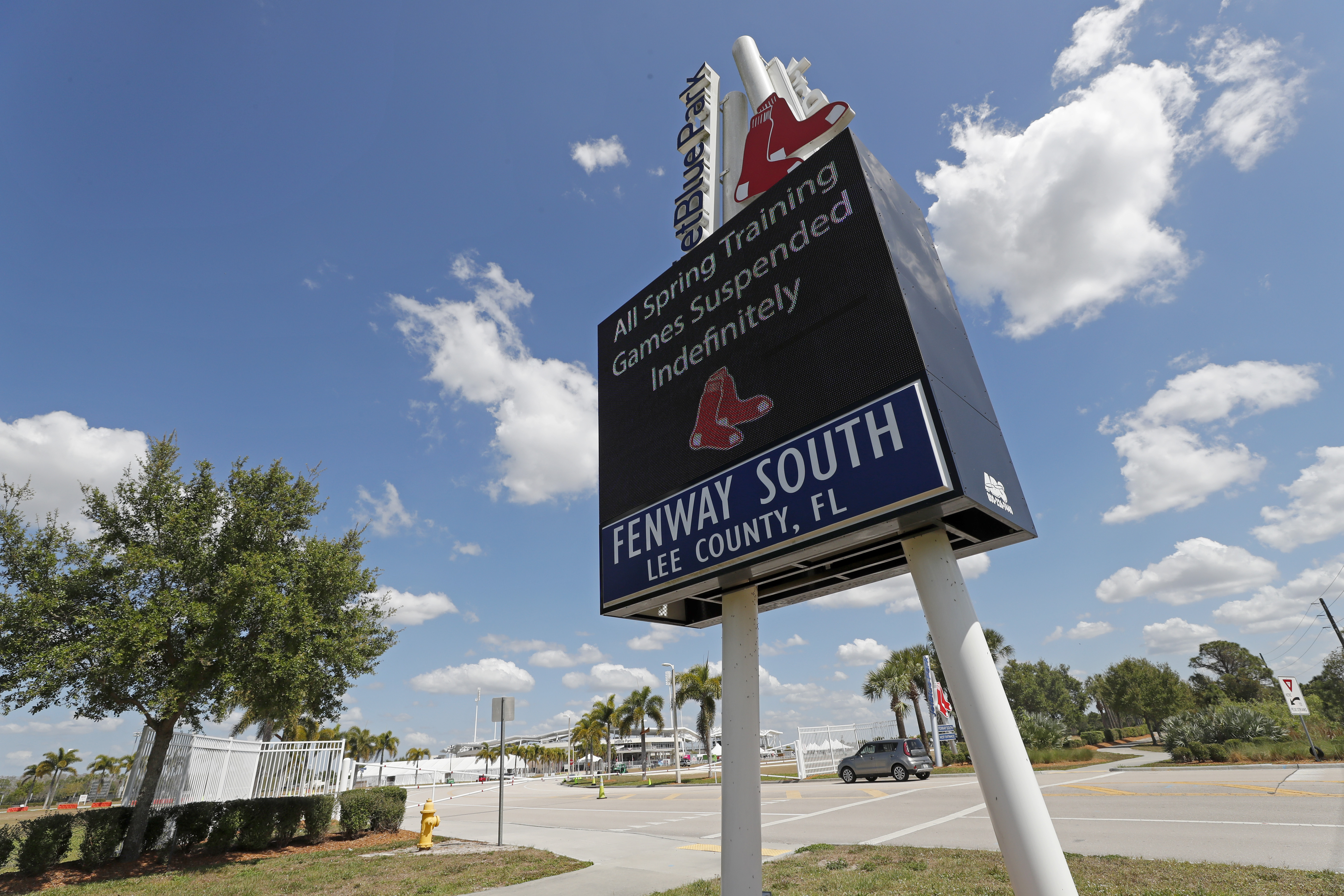 A sign announcing the suspension of spring training baseball games is displayed outside a closed JetBlue Park, the spring training home of the Boston Red Sox in Fort Myers, Fla. on March 13, 2020.