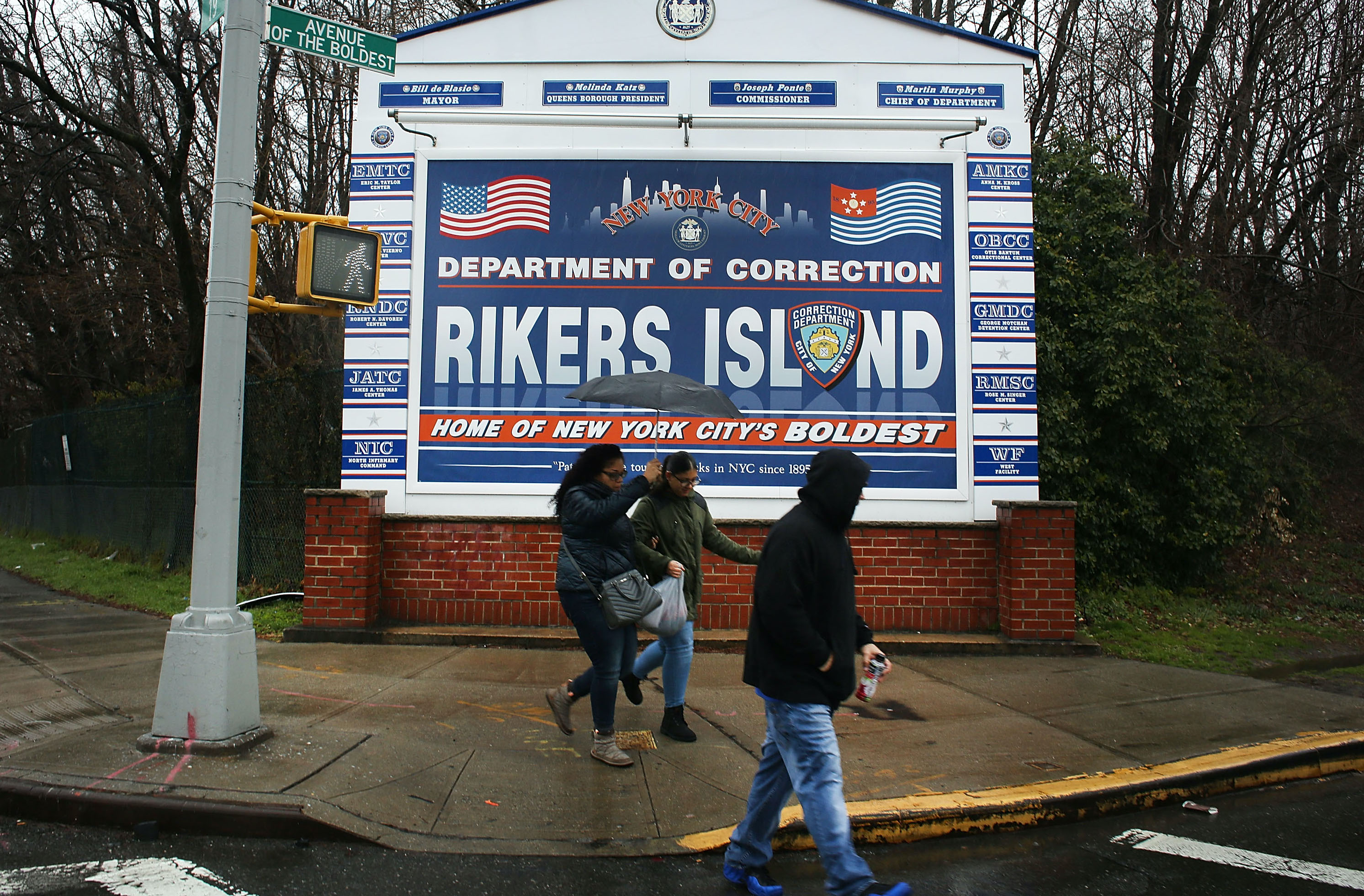 People walk by a sign at the entrance to Rikers Island on March 31, 2017 in New York City.