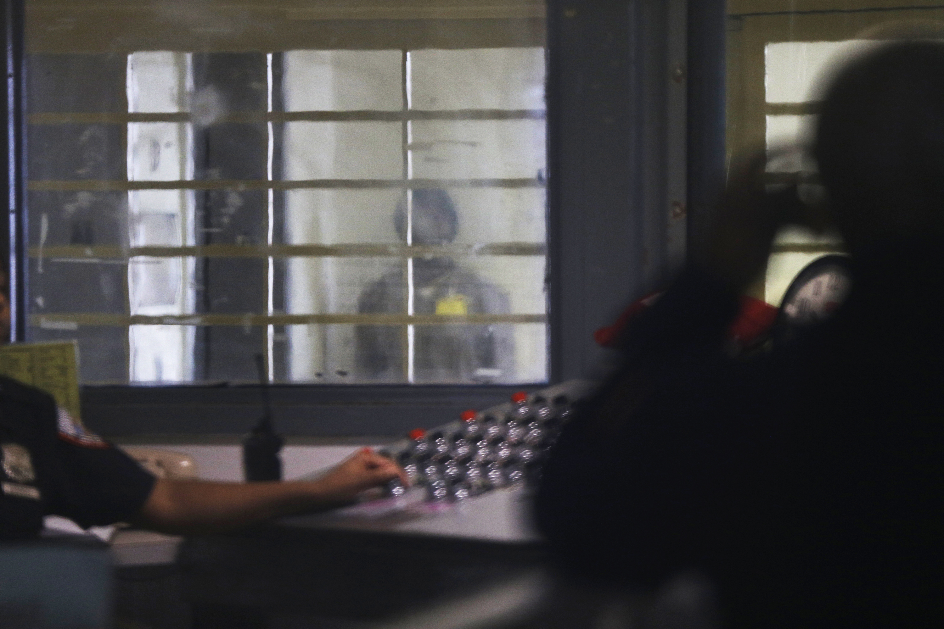 In this March 12, 2015 file photo, a prisoner behind bars and thick plastic looks over at a corrections officer in an enhanced supervision housing unit on Rikers Island in New York.