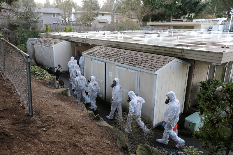 Workers from a Servpro disaster recovery team wearing protective suits and respirators enter the Life Care Center in Kirkland, Wash., to begin cleaning and disinfecting the facility, on March 11, 2020, near Seattle.