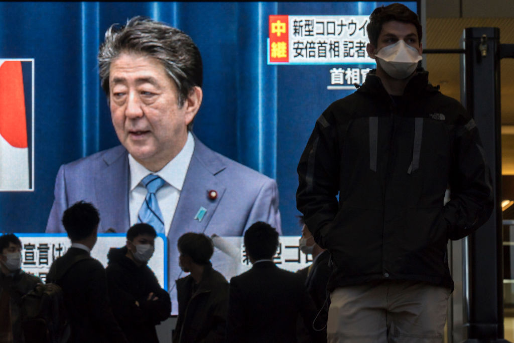 Pedestrians wearing face masks walk past a monitor showing a live broadcast of a press conference by Japanese Prime Minister Shinzo Abe on Covid-19 on March 14, 2020 in Osaka, Japan. Excluding the Diamond Princess cruise ship cases, the number of coronavirus infections in Japan reached 714 on Saturday as United States President Donald Trump suggested the Tokyo Olympics should be postponed to next year.