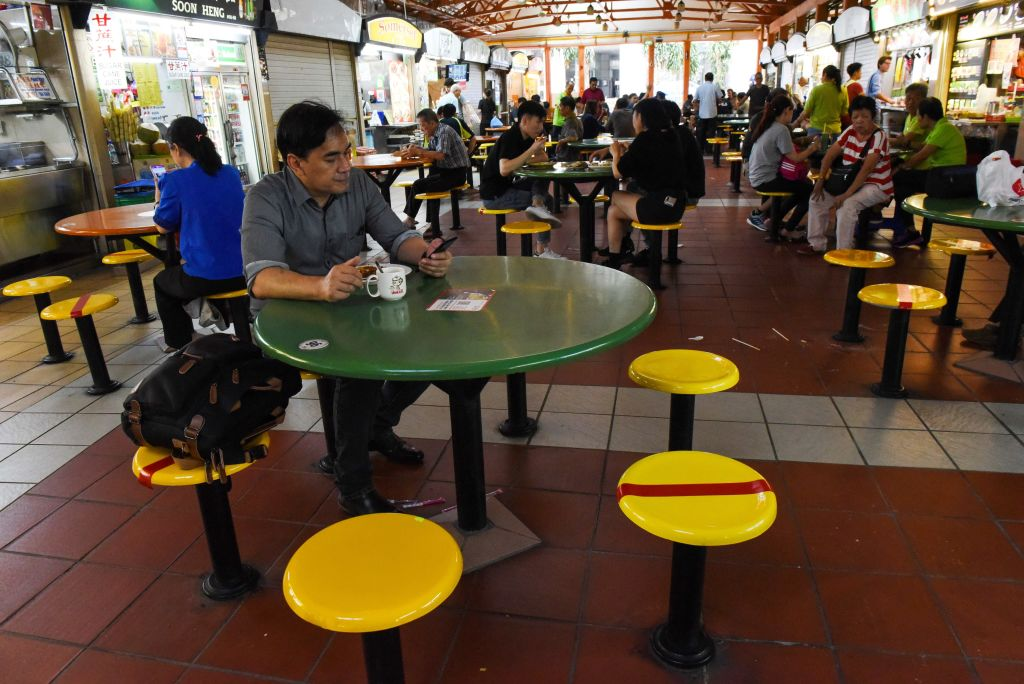 Customers take their meal while some chairs are marked with red tapes as authorities implement social distancing at a hawker centre, amid fears about the spread of the COVID-19 novel coronavirus in Singapore on March 18, 2020.