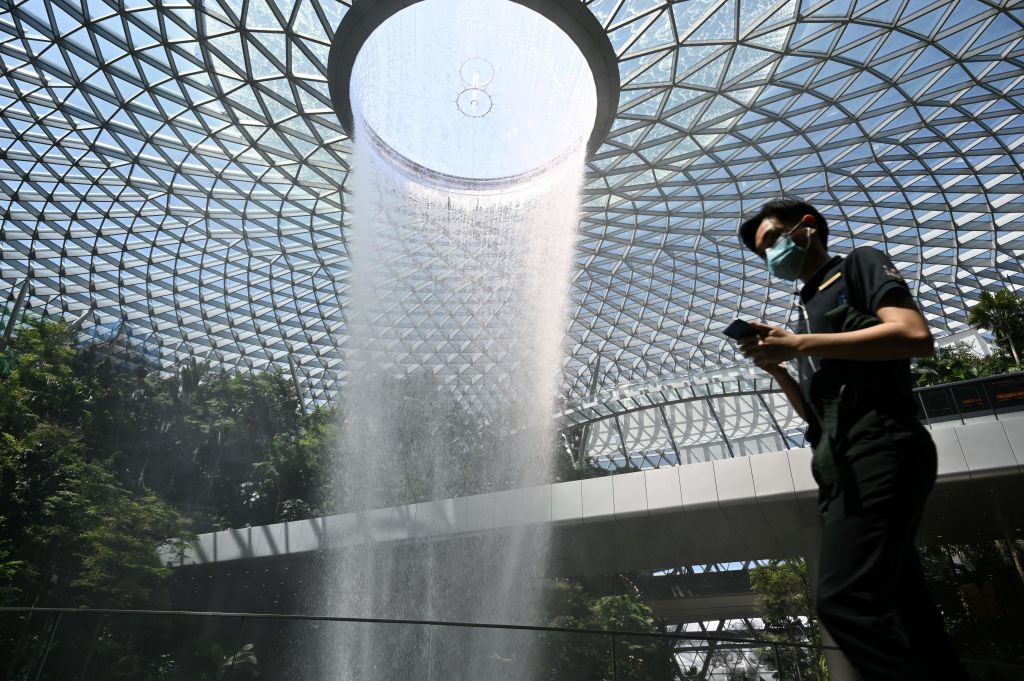 A man wearing a facemask walks past the Rain Vortex display at the airport in Singapore on Feb. 27, 2020.