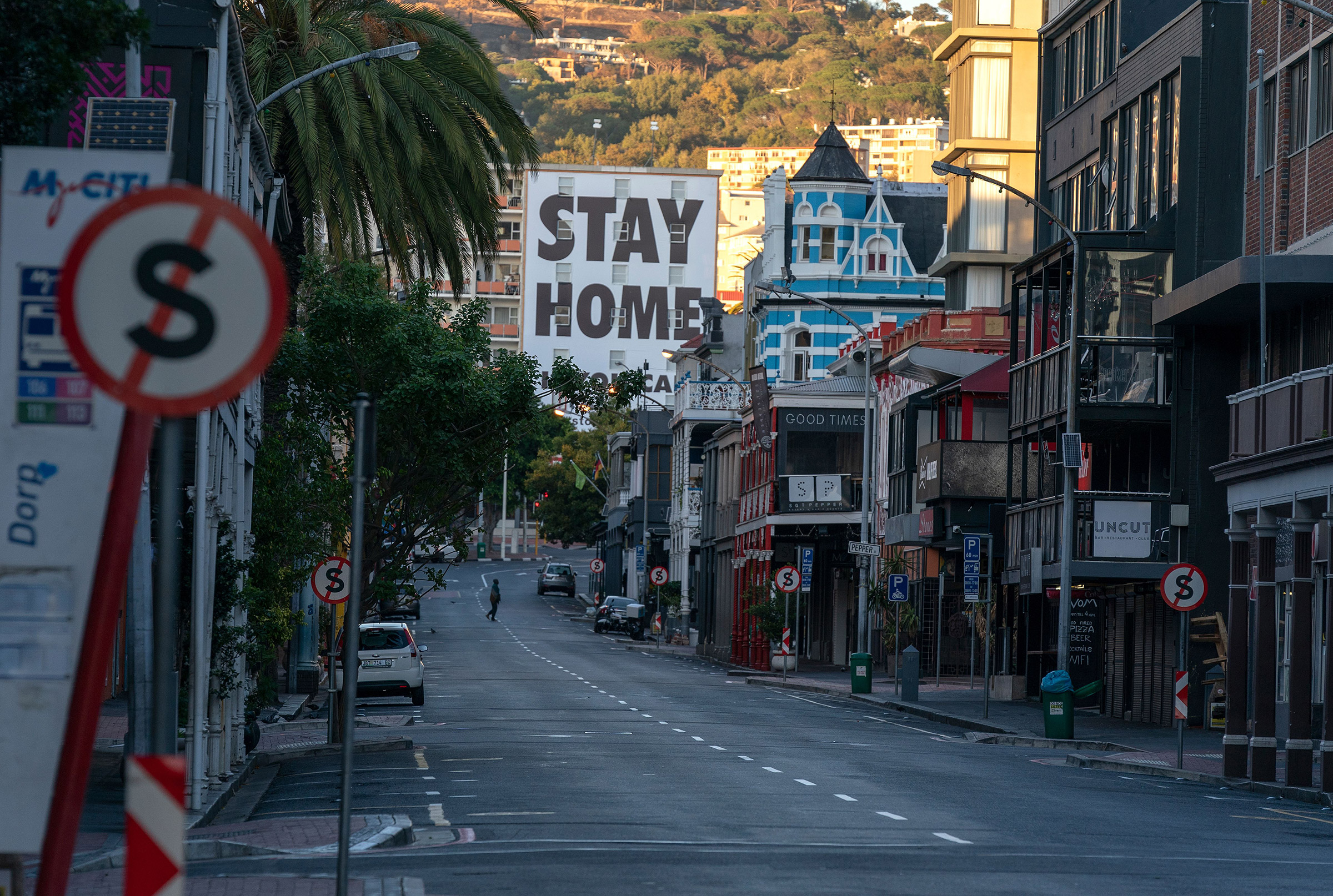 A man crosses a deserted street during day one of a 21-day national total lockdown in Cape Town on March 27, 2020.
