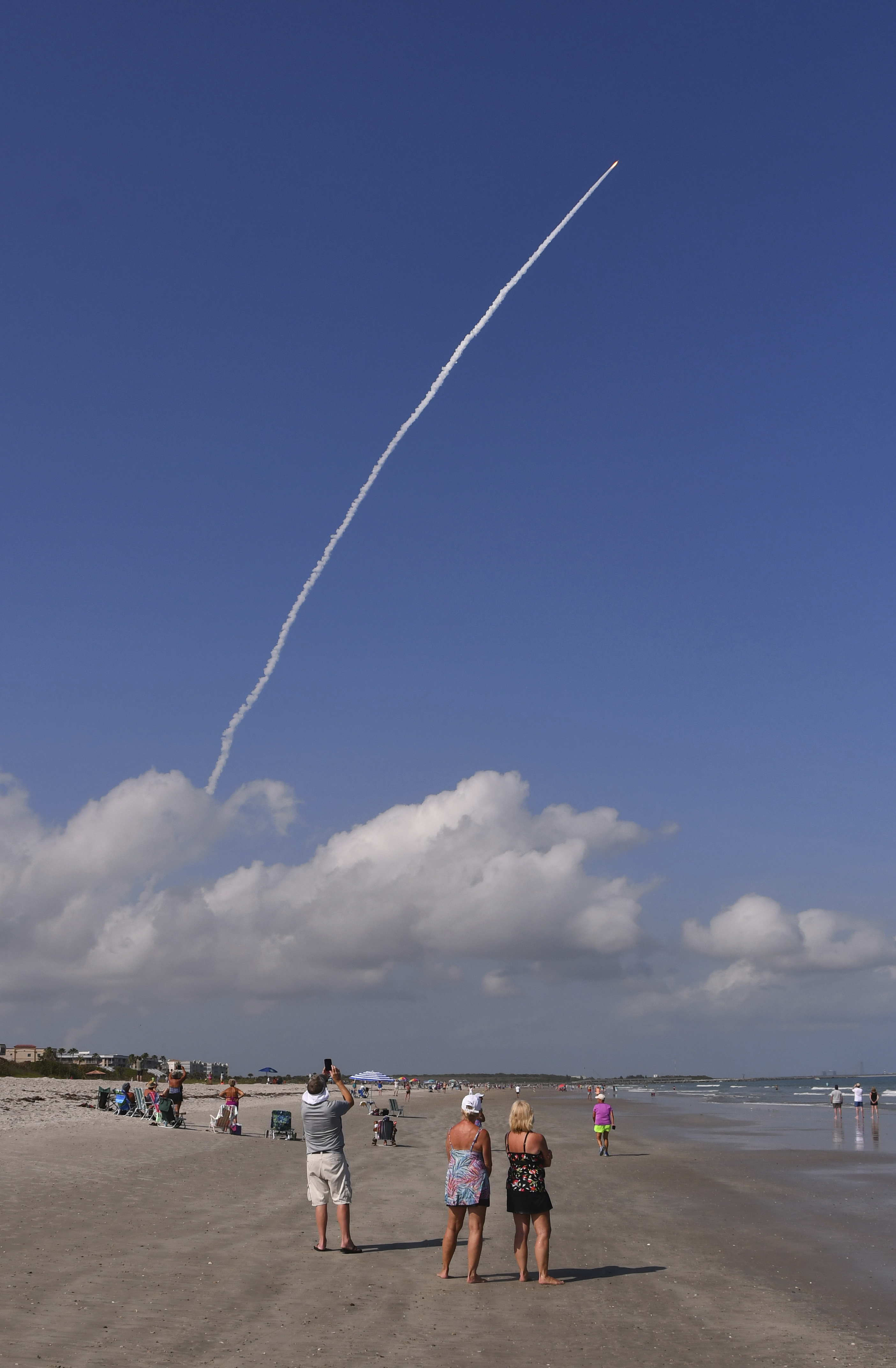 Sparse crowds on the beach watch the launch of an Atlas V rocket carrying a satellite, the sixth and final one in the U.S. military's Advanced Extremely High Frequency series, Thursday, March 26, 2020, from Cape Canaveral, Fla.