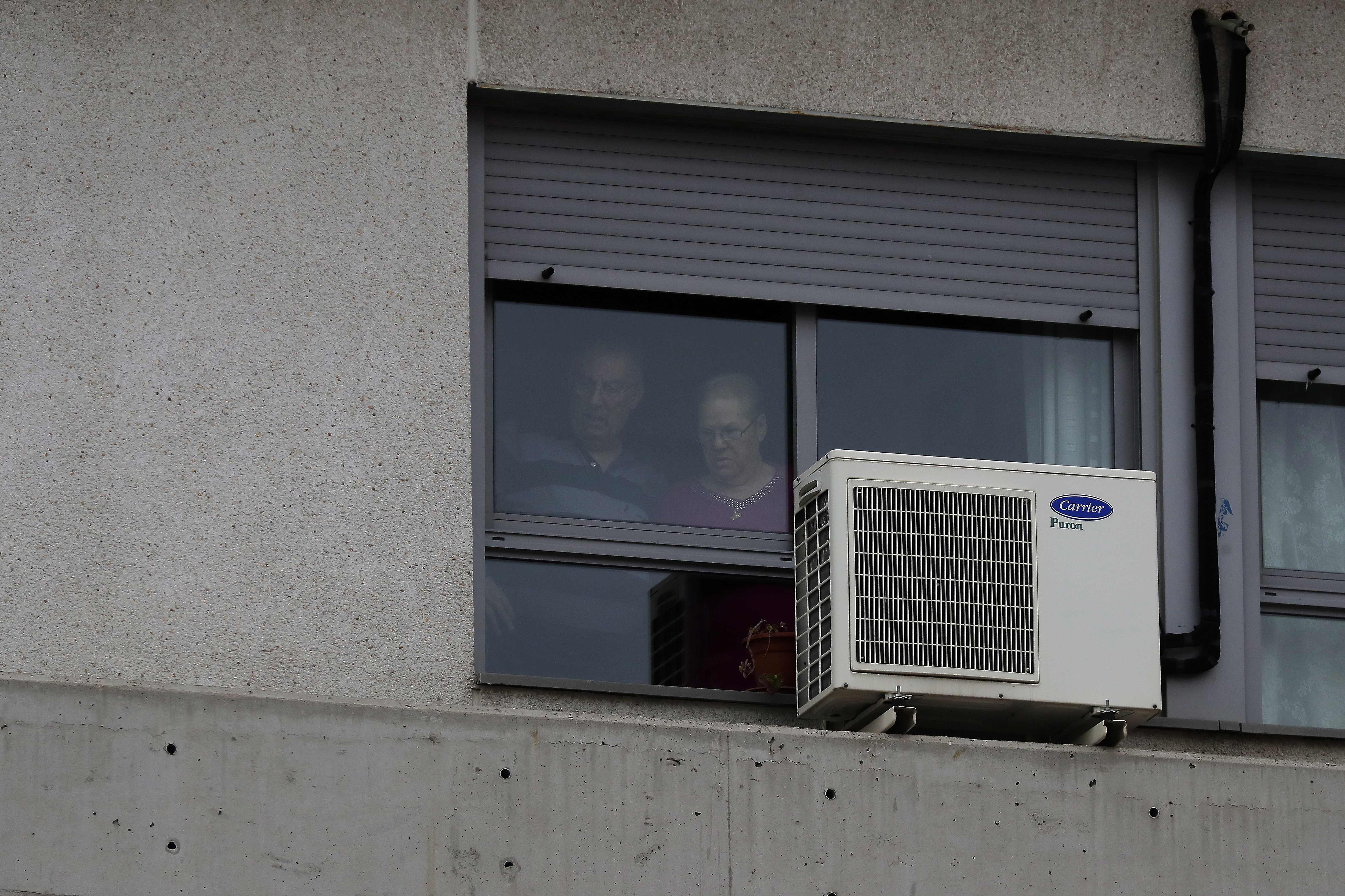 People look out from a window inside of a nursing home where dead bodies were found at the nursing homes of Usera in Madrid, Spain, Tuesday, March 24, 2020.