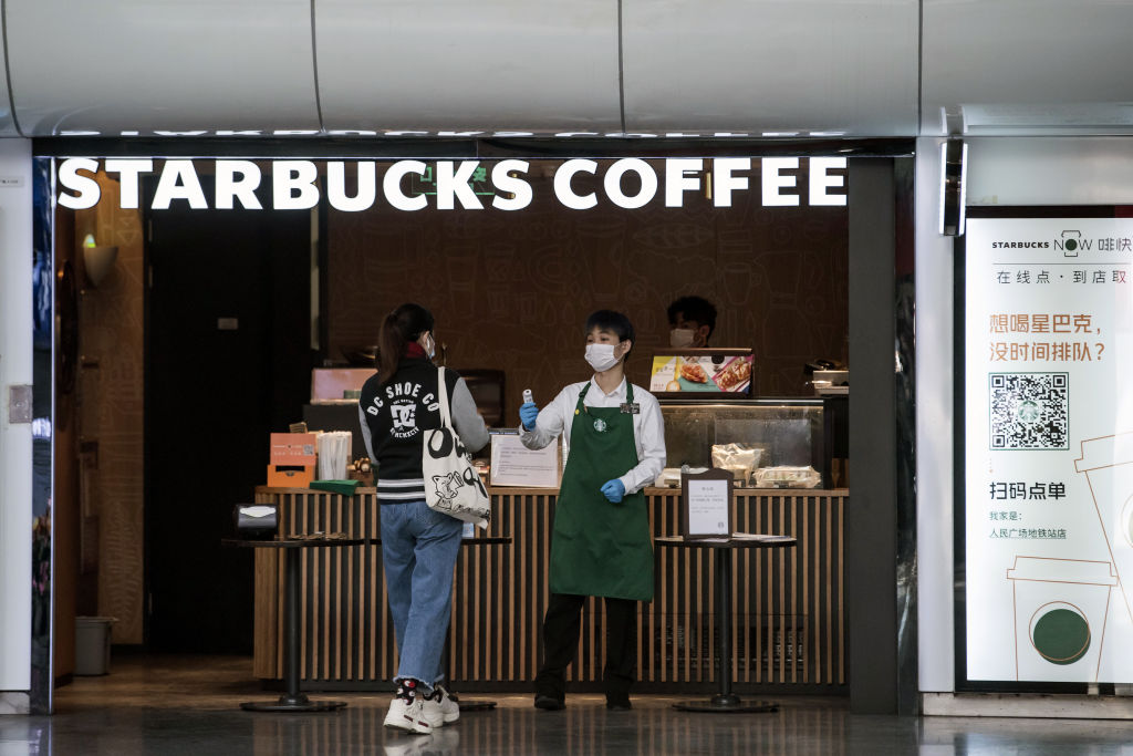 An employee checks the temperature of a customer at the entrance of a Starbucks Corp. coffee shop in Shanghai, China on March 2, 2020.