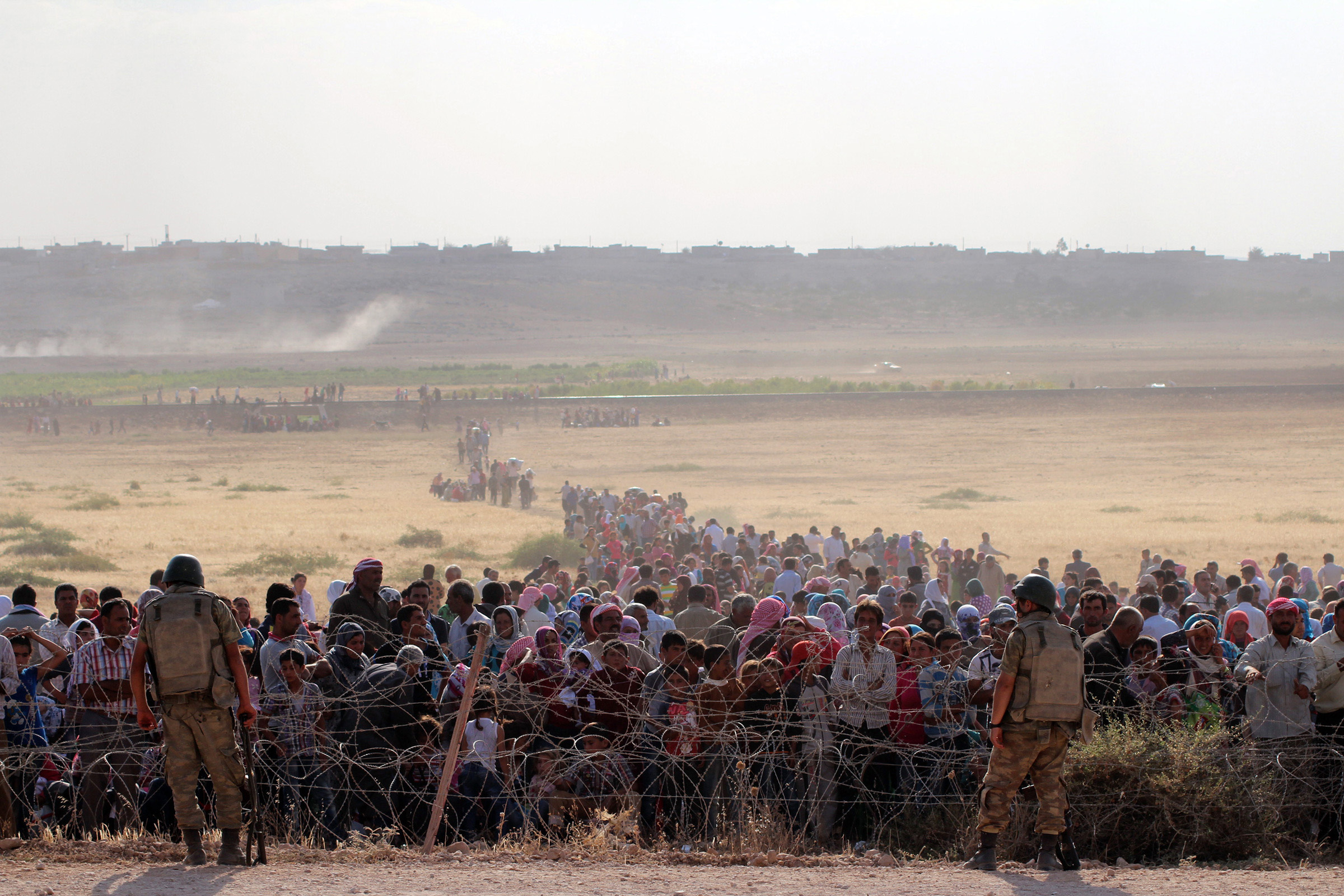 Syrians fleeing from clashes between the Islamic State of Iraq and Syria (ISIS) militants wait at the Turkish-Syrian border to cross into Turkey on Sept. 18, 2014.