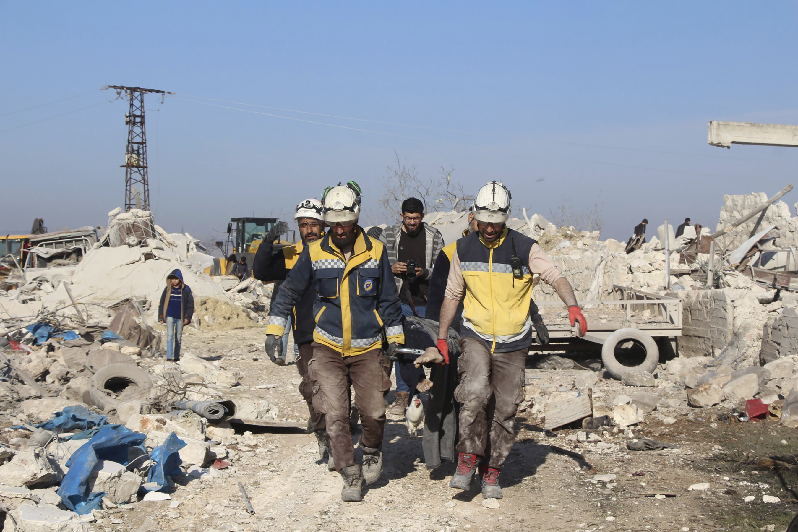 Civil defense workers carry a victim next to houses destroyed by airstrikes, in Maaret Musreen village, Idlib province, Syria, on March 5, 2020.