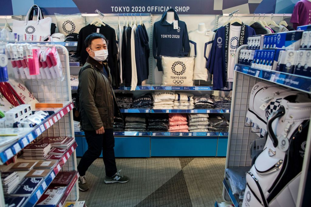 A man wearing a face mask, amid concerns over the spread of the COVID-19 novel coronavirus, visits a Tokyo 2020 official shop in Tokyo on March 25, 2020, the day after the historic decision to postpone the 2020 Tokyo Olympic Games.