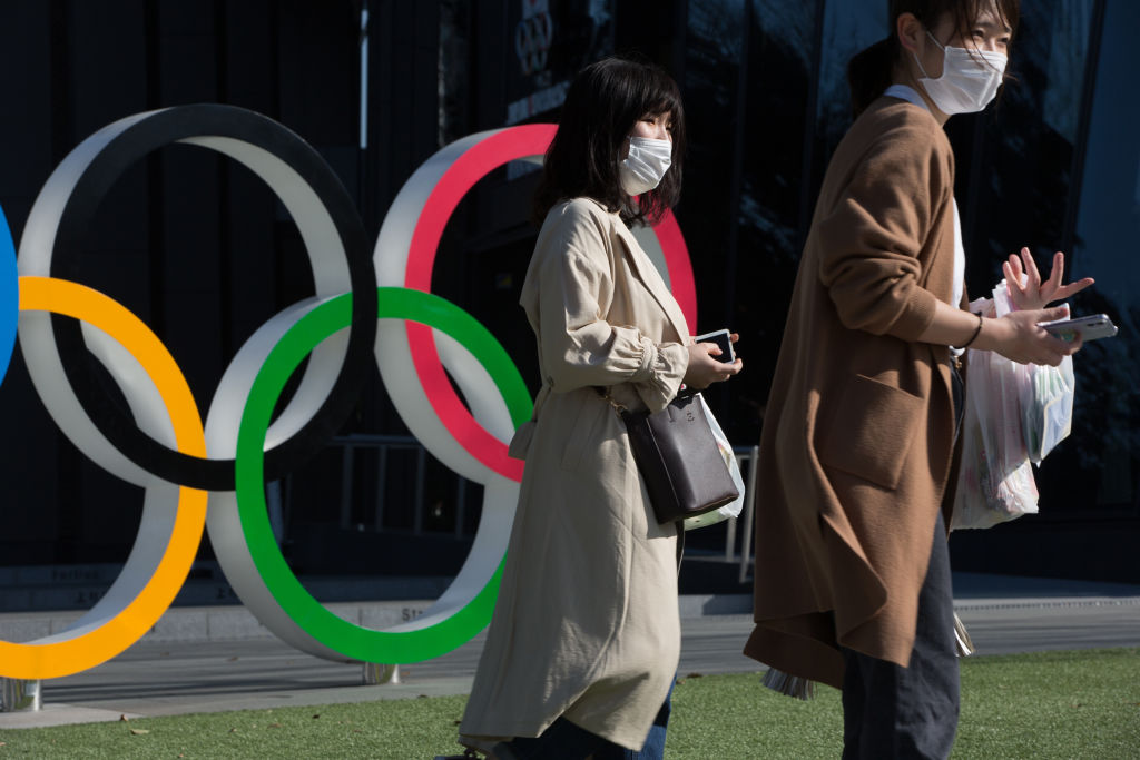 Women with surgical masks walk next to the Olympic Rings in front of the Japan Olympic Museum in Shinjuku.