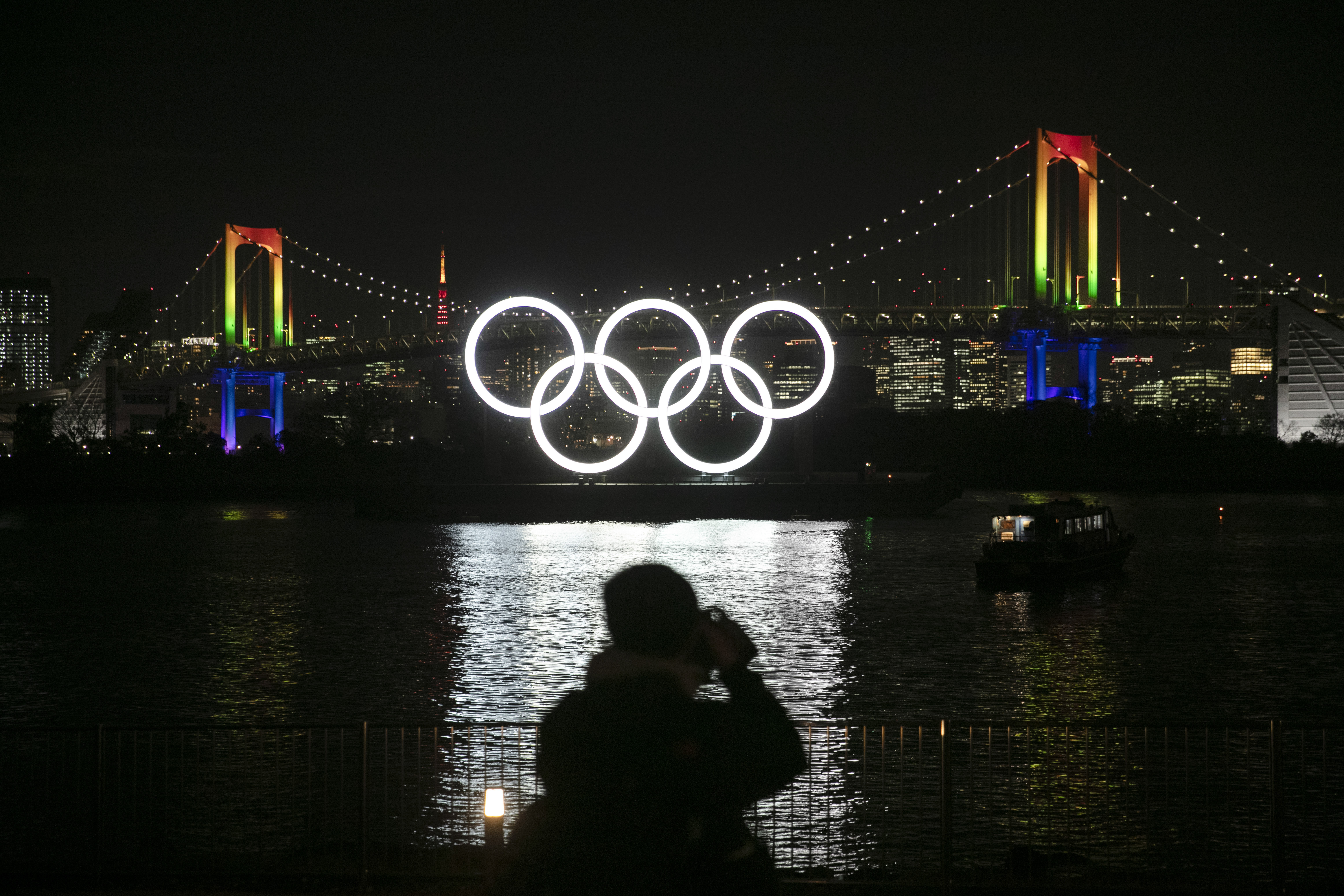 A photographer takes pictures of the illuminated Olympic rings in front of the Rainbow Bridge on Jan. 24, 2020, in Tokyo, Japan.