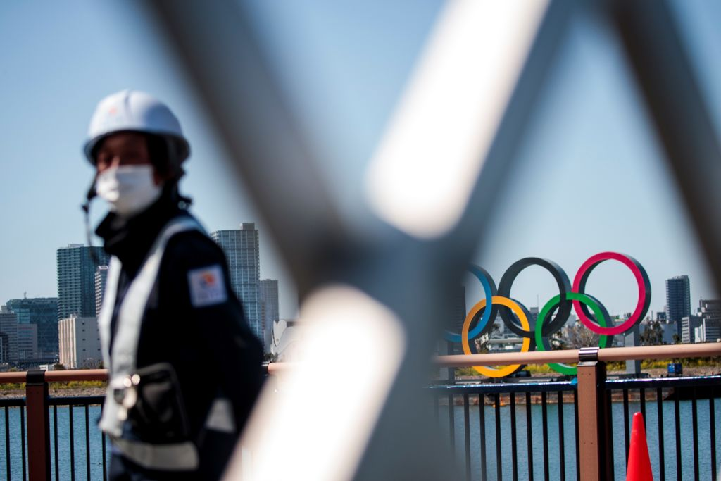 A construction worker looks on near the Olympic rings in Tokyo's Odaiba district on March 25, 2020, the day after the historic decision to postpone the 2020 Tokyo Olympic Games.