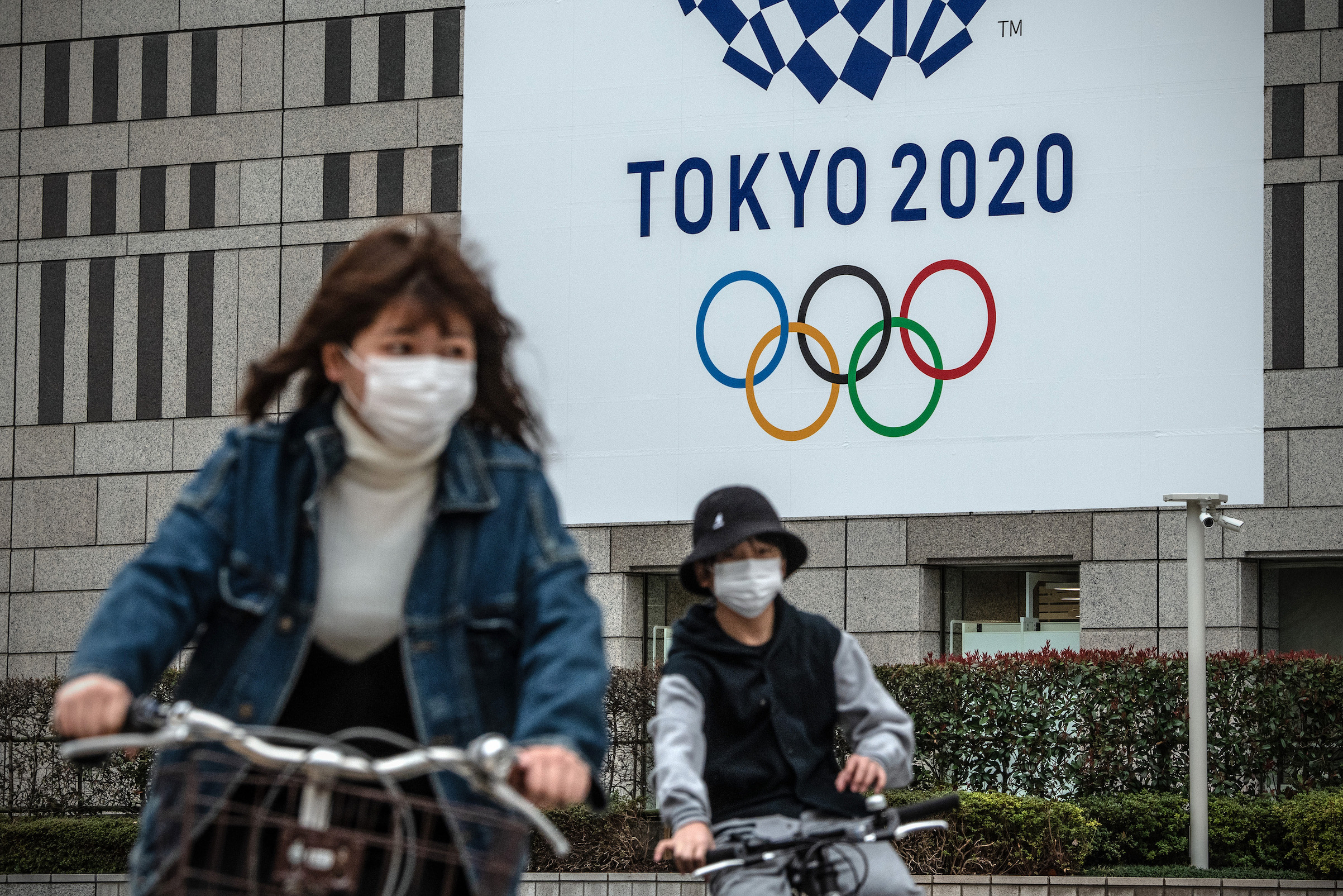People cycle past a banner for the Tokyo Olympics on March 13 in Tokyo