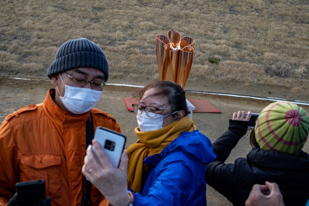 People take pictures in front of the Tokyo 2020 Olympic flame on display at Ishinomaki Minamihama Tsunami Recovery Memorial Park in Japan on March 20, 2020.