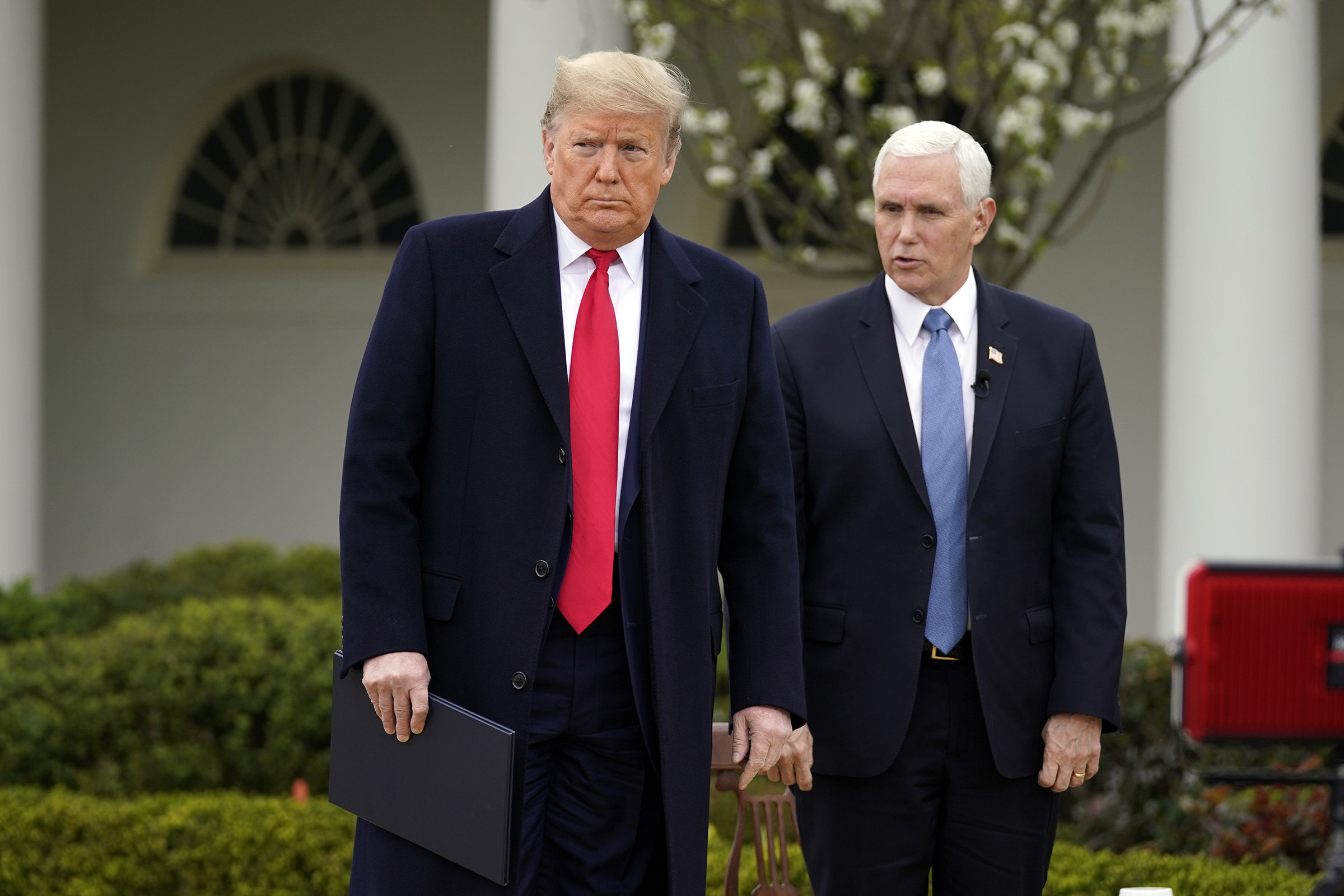 President Donald Trump speaks with Vice President Mike Pence at the White House, on March 24, 2020, in Washington.