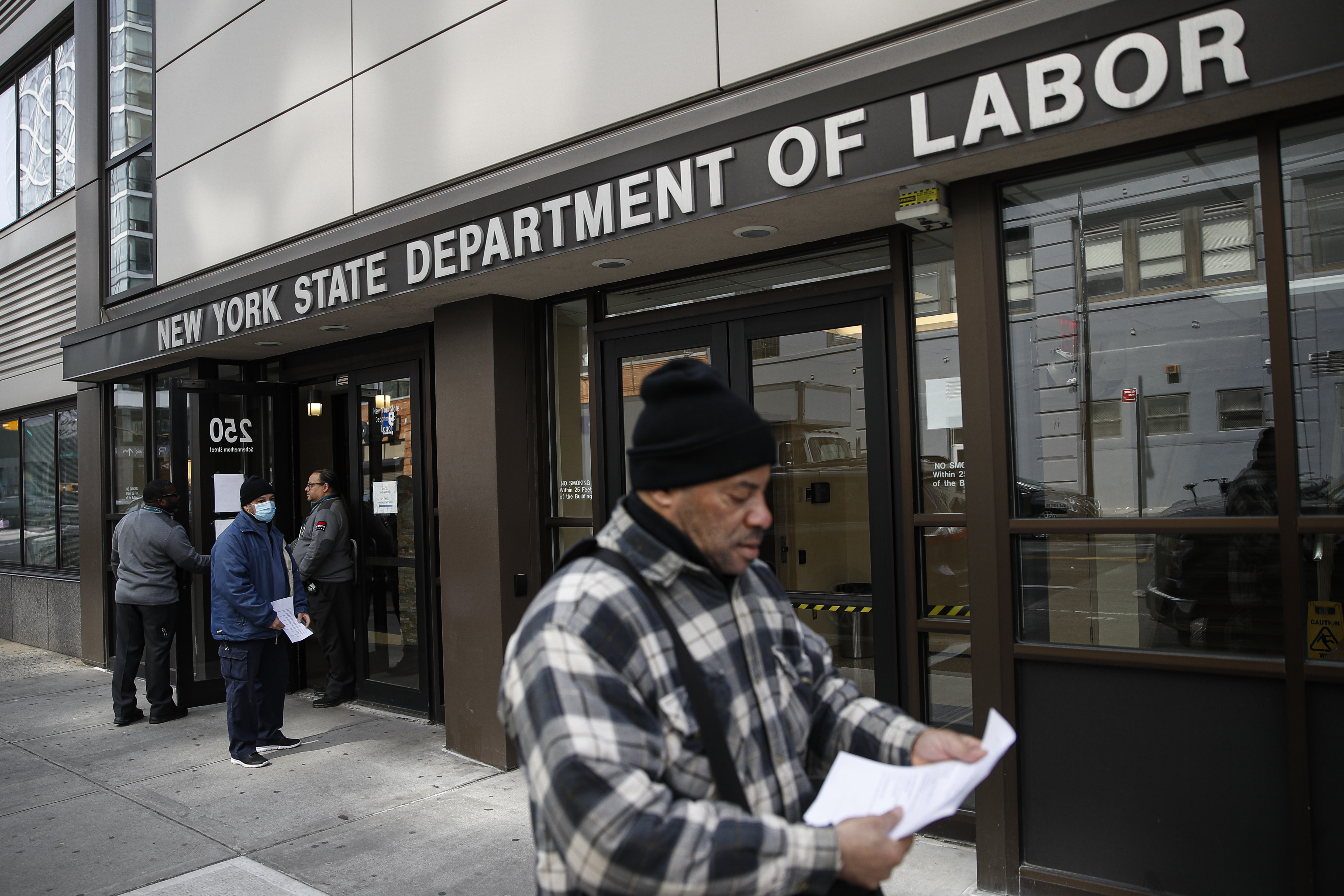 Visitors to the Department of Labor are turned away at the door by personnel due to closures over coronavirus concerns on March 18, 2020, in New York.
