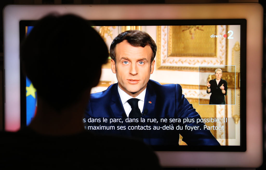 French President Emmanuel Macron is seen on a television screen as he speaks during a televised address to the nation on the outbreak of COVID-19, caused by the novel coronavirus, on March 16, 2020, in Paris.