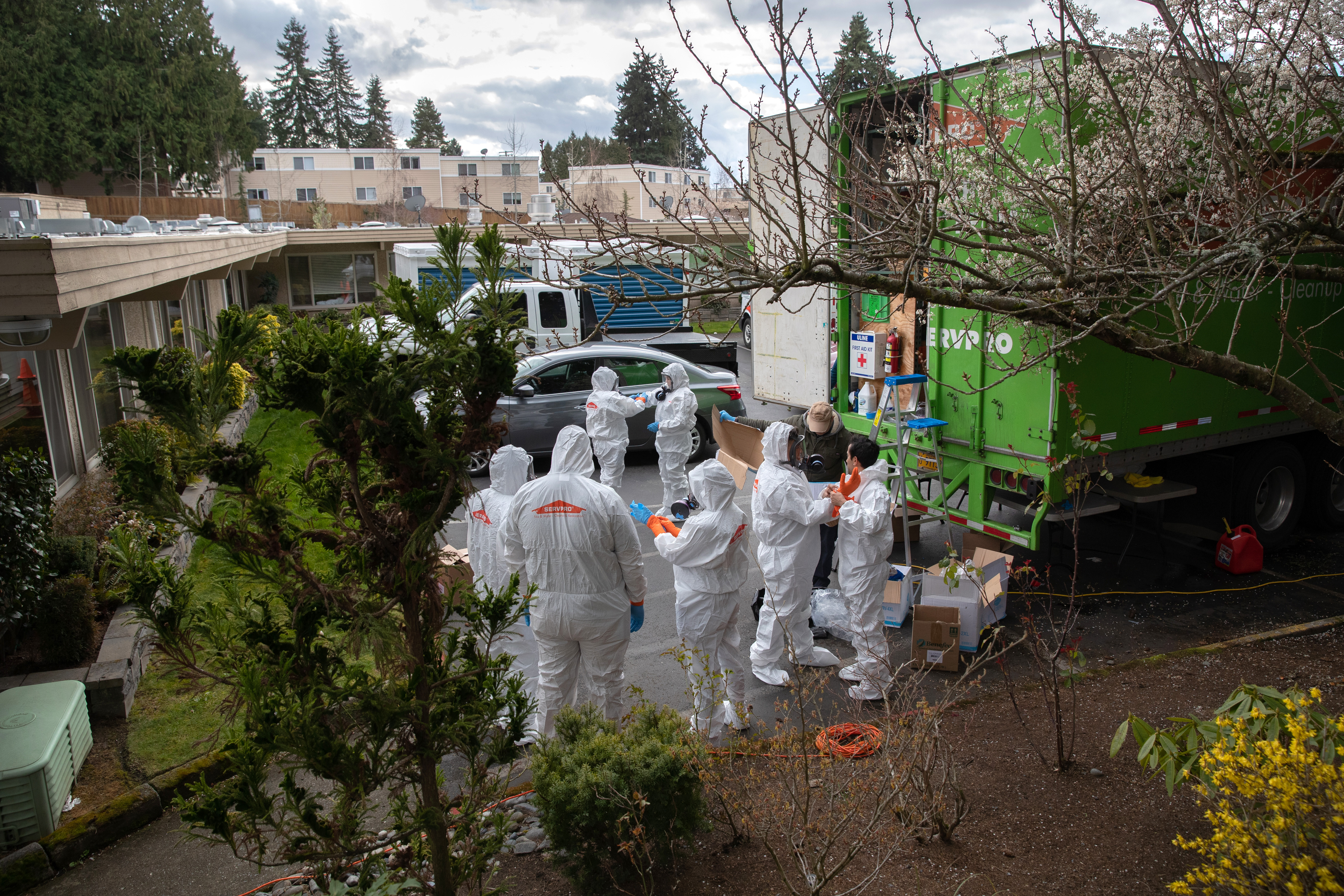 A cleaning crew wearing protective clothing (PPE) to protect them from coronavirus prepares to enter the Life Care Center on March 12, 2020 in Kirkland, Washington.