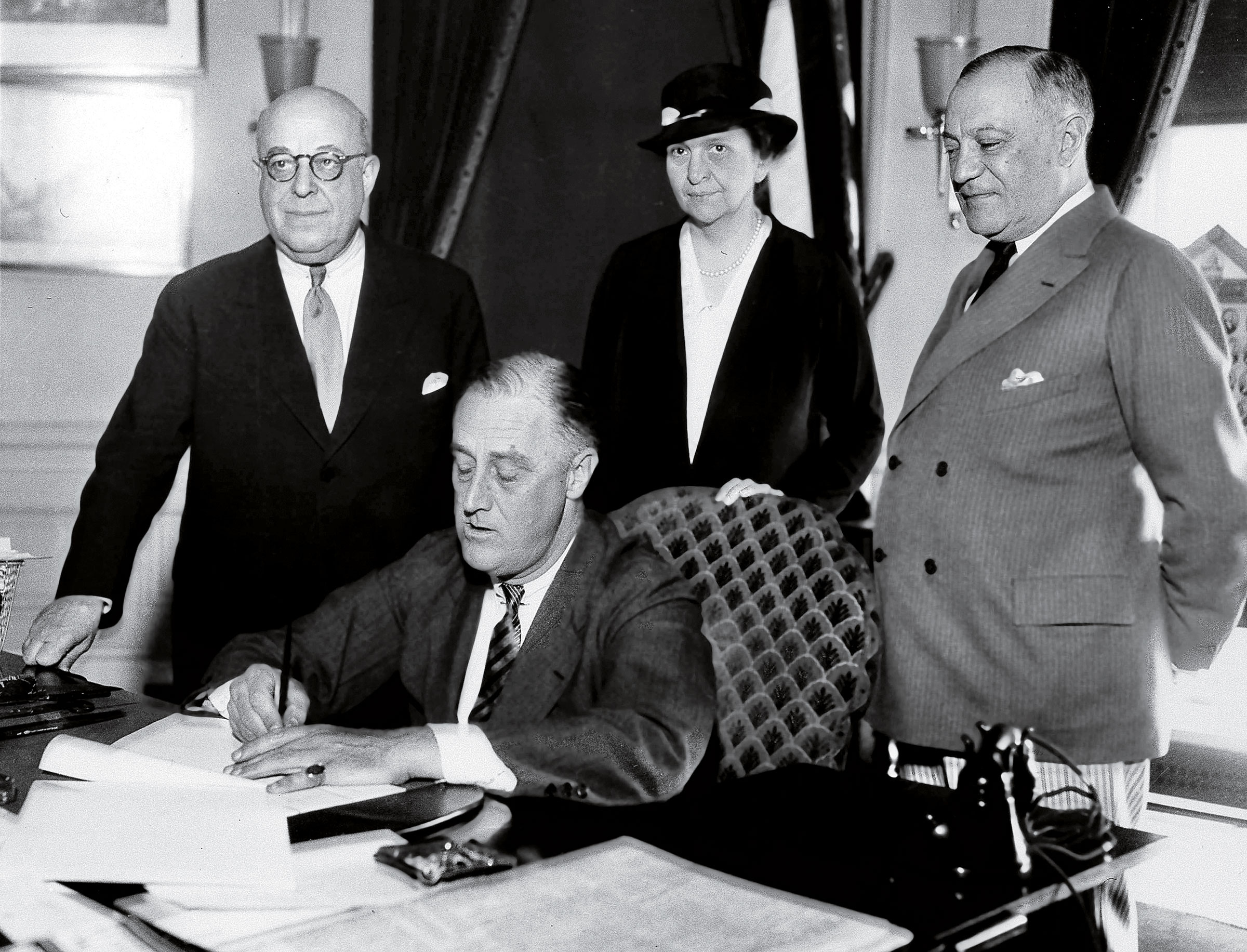 Perkins, behind President Roosevelt as he signs part of the New Deal into law on June 6, 1933.