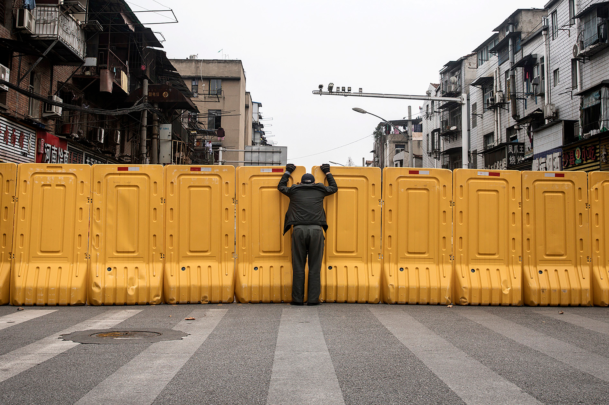 A man talks to another man through a makeshift barricade, built to control entry and exit to a residential compound, in Wuhan, China, on March 8.