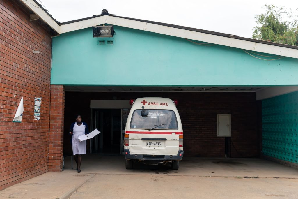 A nurse walks past one of the only three working ambulances at the Zengeza Clinic in Chitungwiza on March 20, 2020.