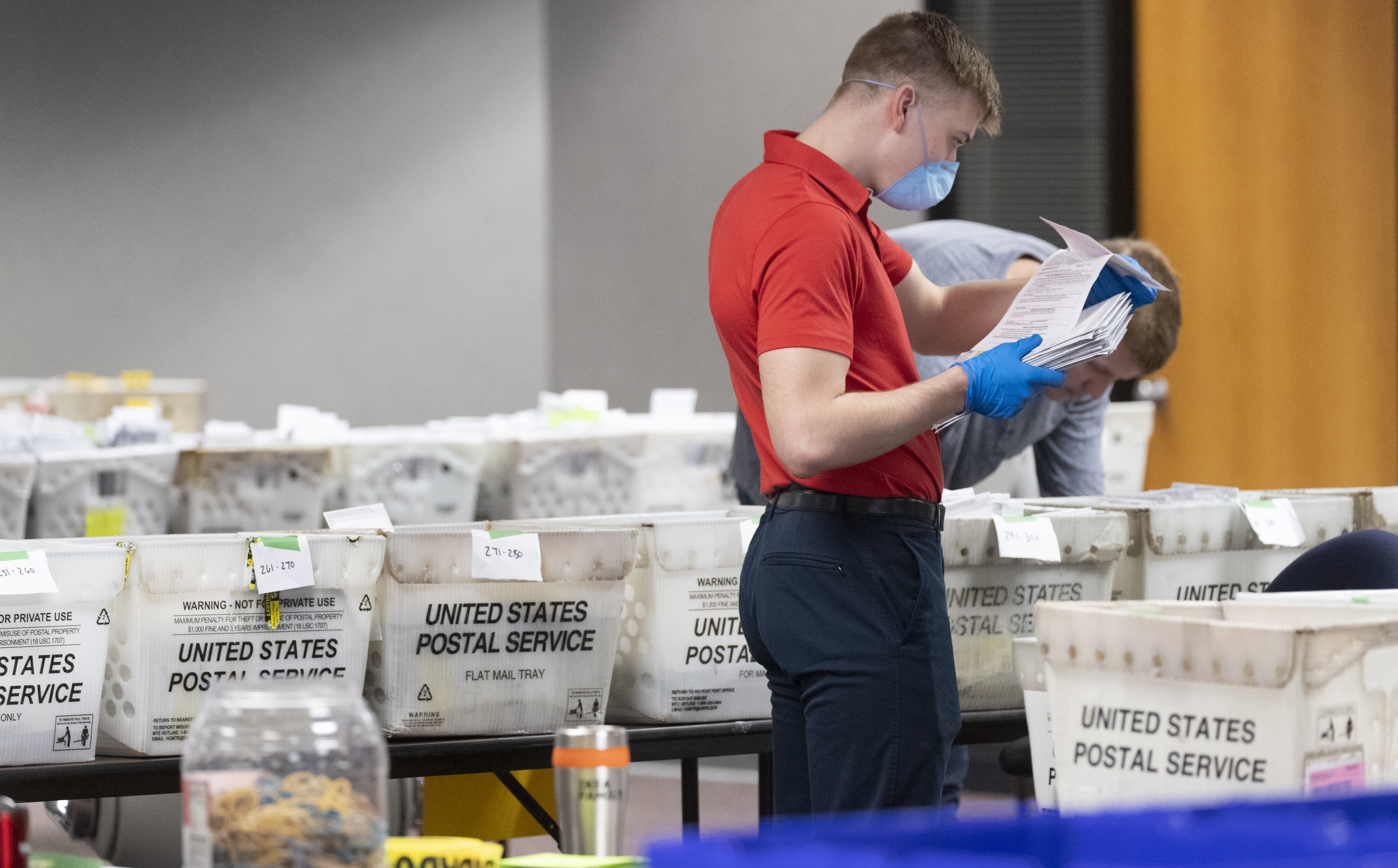 A City of Milwaukee Election Commission worker processes and sorts absentee ballots for Tuesday's primary election on April 8, 2020, in downtown Milwaukee, Wis.