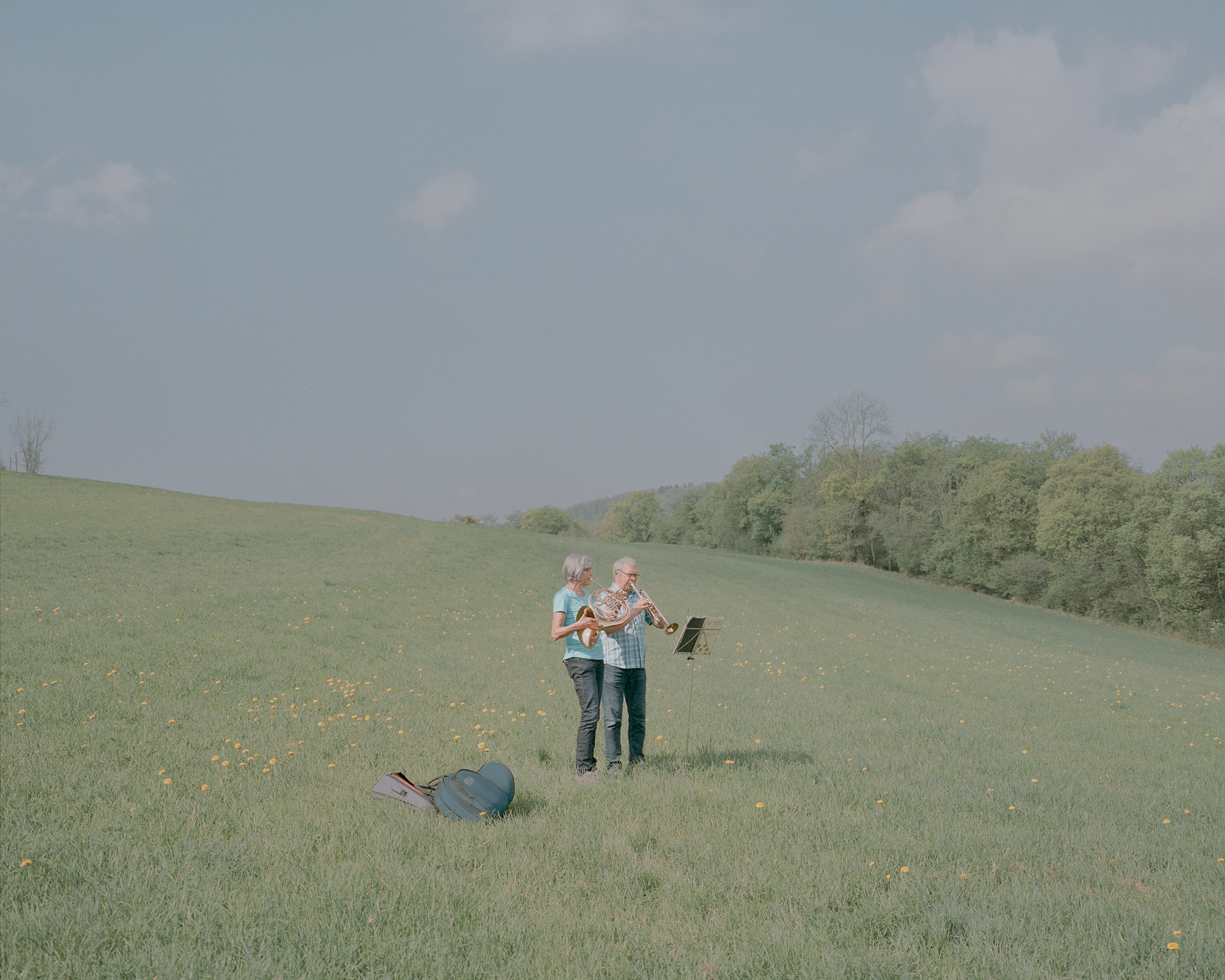 "Every Sunday, members of a church brass band  Posaunenchor Essingen"" play at the same time around the town Essingen, as they cannot meet in person. Andrea and Rainer Zube, pictured here on April 19, play in a meadow."