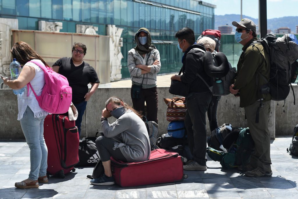 Travelers wait in line for a charter flight coordinated by the United States embassy to take them home at the La Aurora international airport in Guatemala City on March 23, 2020.