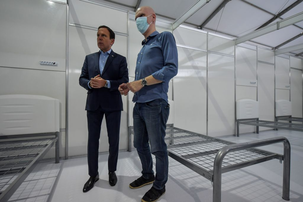 Sao Paulo state Governor Joao Doria (L) and Sao Paulo city Mayor Bruno Covas (R) visit a field hospital set up for coronavirus patients at Pacaembu stadium, in Sao Paulo, Brazil on March 27, 2020