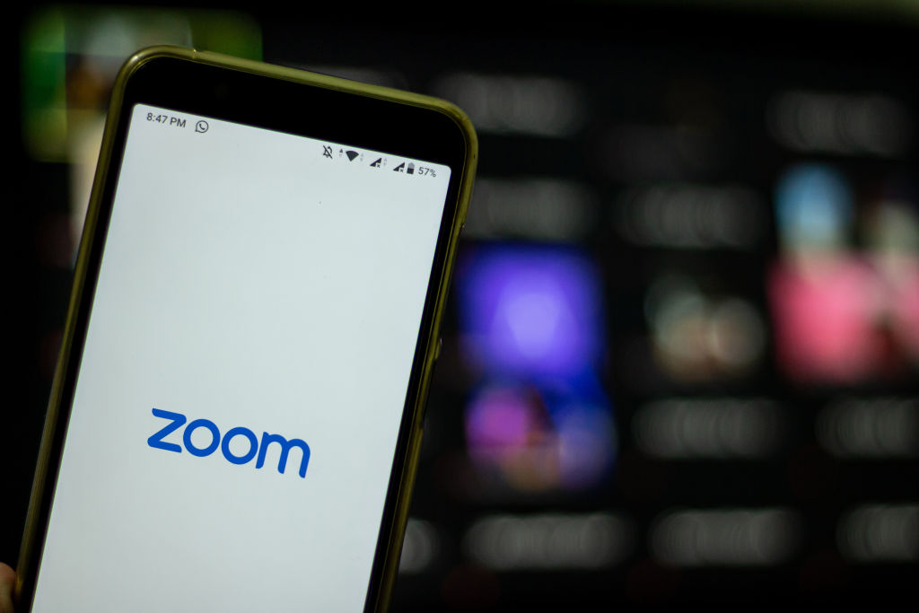 Logo of Zoom, the video conferencing application services company, is seen with the group chat in the back of it in Yogyakarta, Indonesia on April 3, 2020.