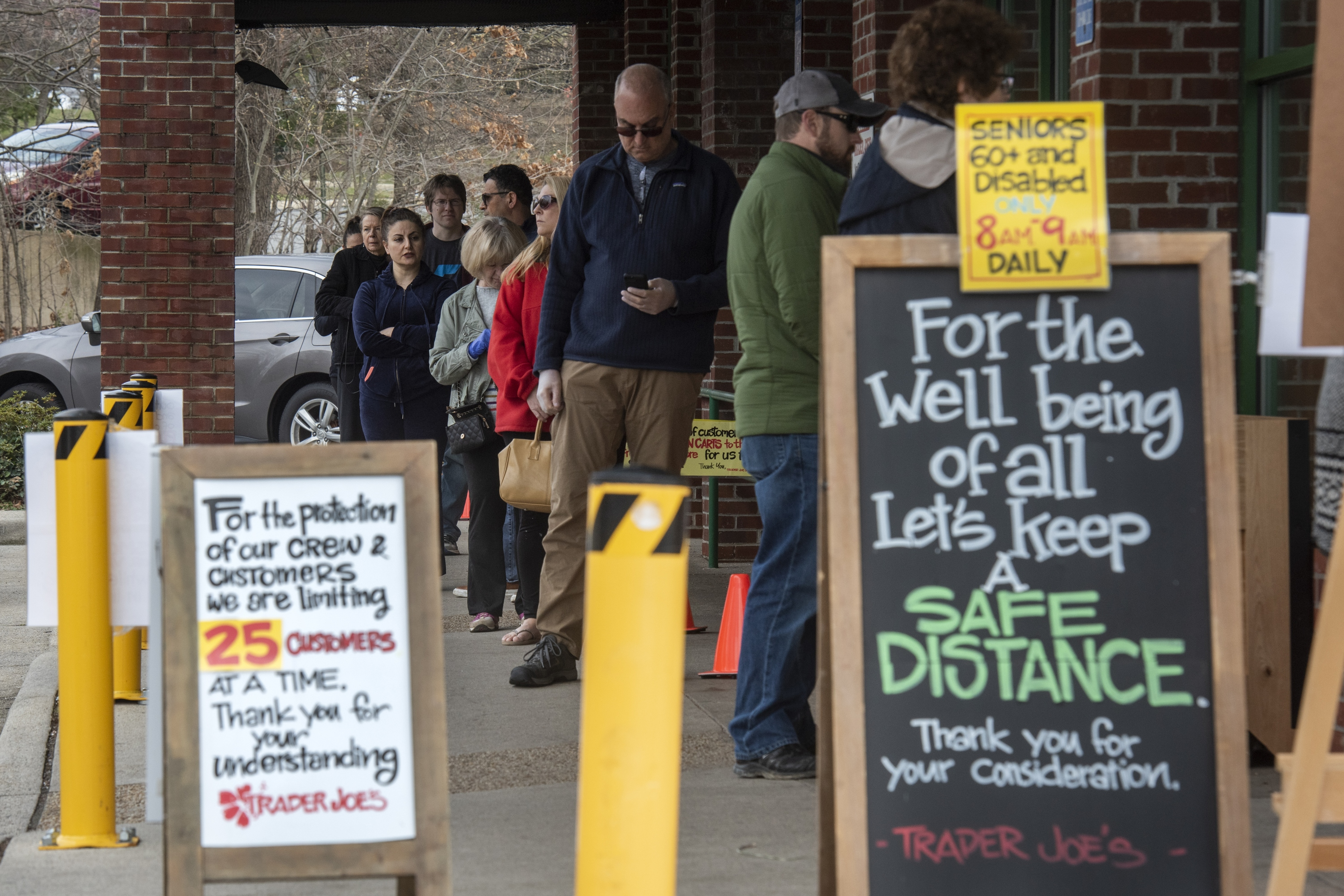 A sign reminds people to observe social distancing rules as they wait to enter a grocery store in Reston, Virginia, on April 1, 2020.