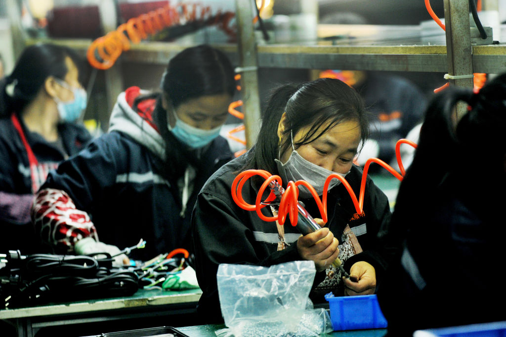 Workers assemble products in a factory of LED lights in Yushan county in central China's Jiangxi province Sunday, April 12, 2020.