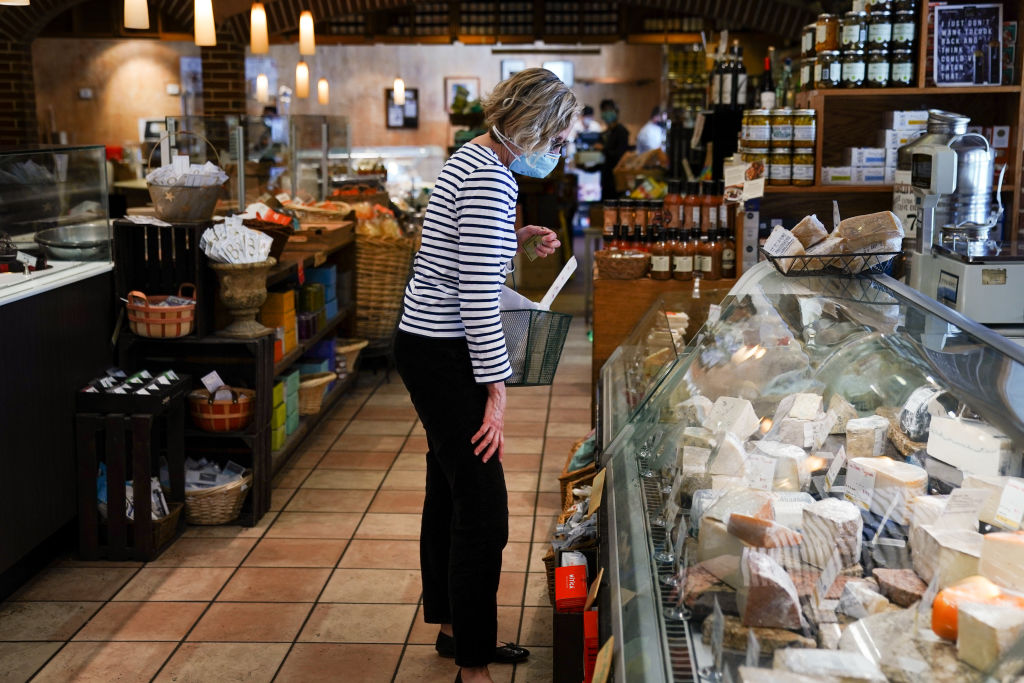 A customer wears a protective mask while shopping for cheese at a market in Atlanta, Ga., on May 1, 2020.