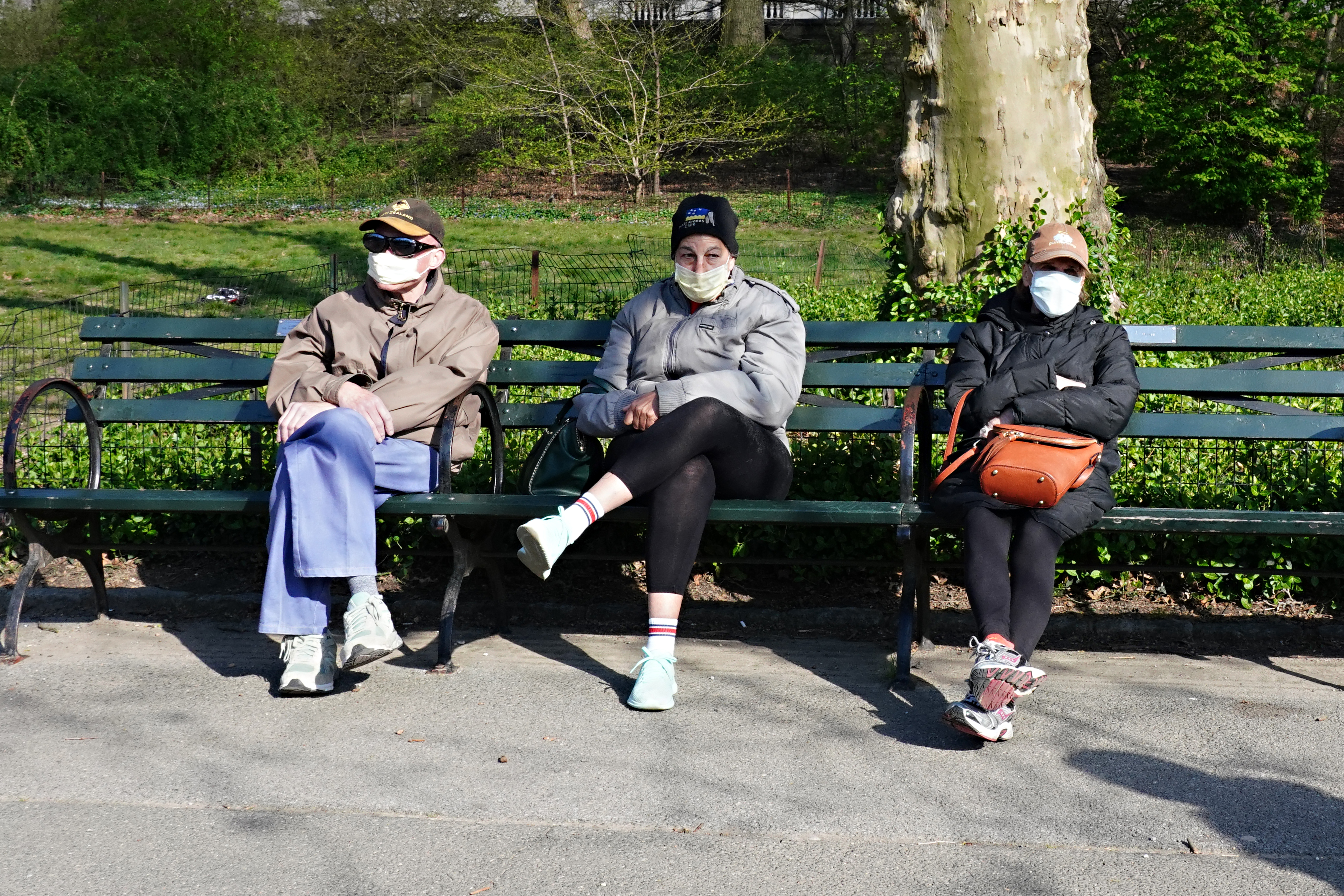 New Yorkers heed advice to wear masks to help control the spread of the coronavirus as they sit in Central Park in New York City on April 11, 2020.