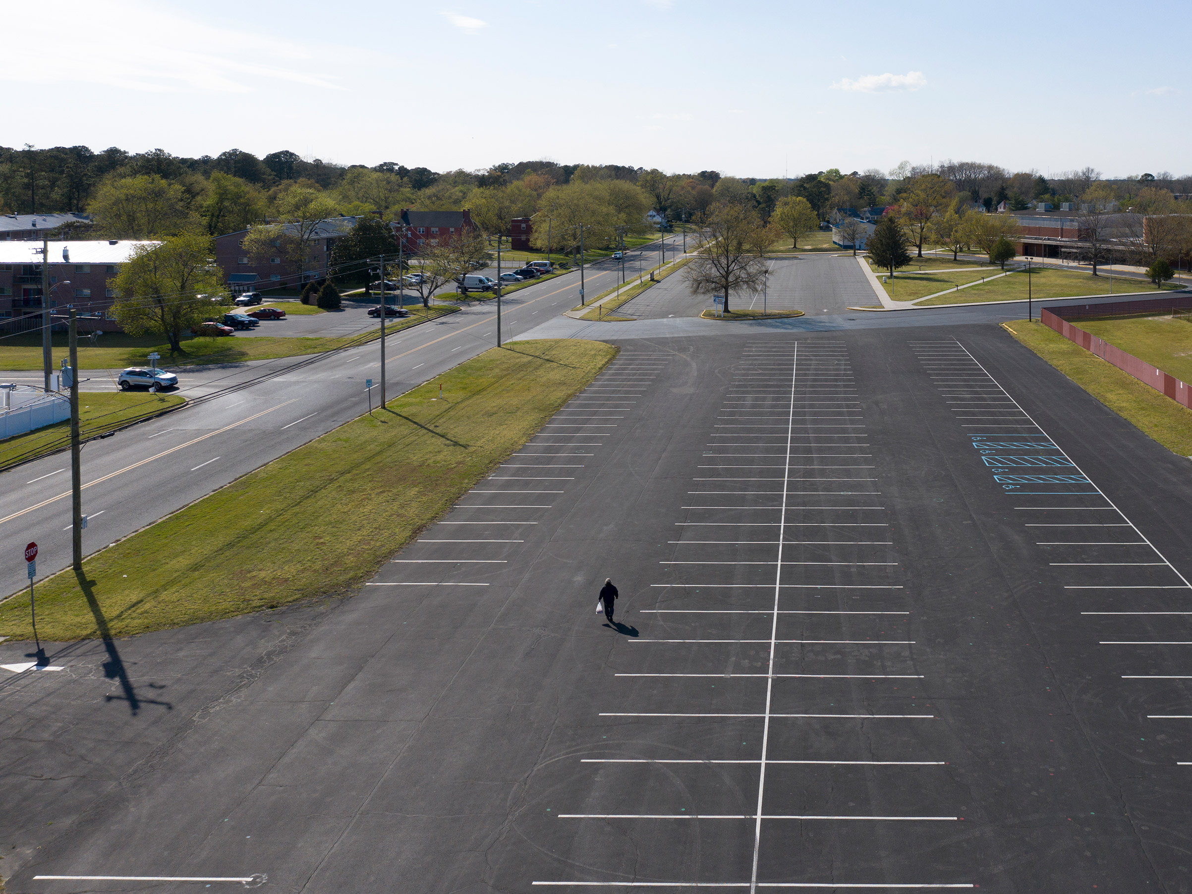 Pandemic lockdowns have                       brought life to a halt in                       towns like Salisbury, Md.,                       pictured here on April 11,                       emptying normally                       teeming public spaces                       like the parking lot of the                       Wicomico High School and                       stadium, right.