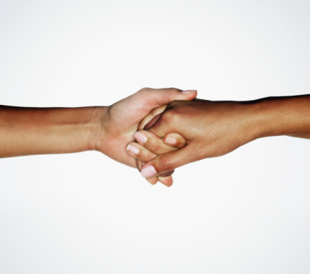 Two young women linking hands