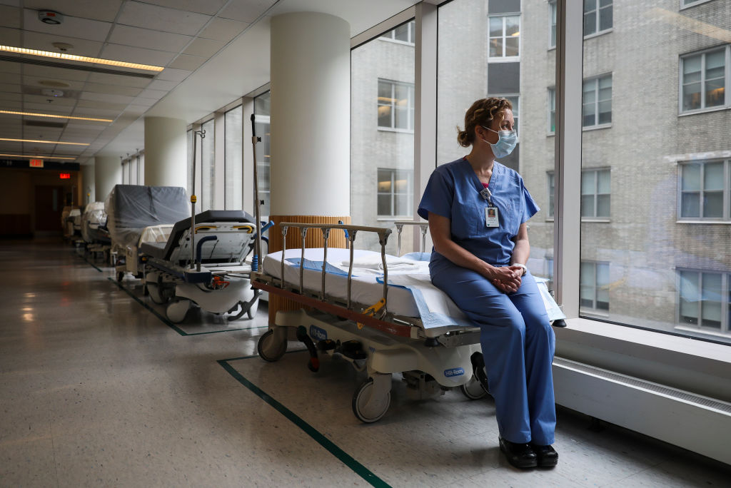 Christine McCarthy, a nurse for over 20 years and a palliative nurse for the past year, sits for a portrait on an empty hospital bed at Massachusetts General Hospital in Boston on Apr. 2.