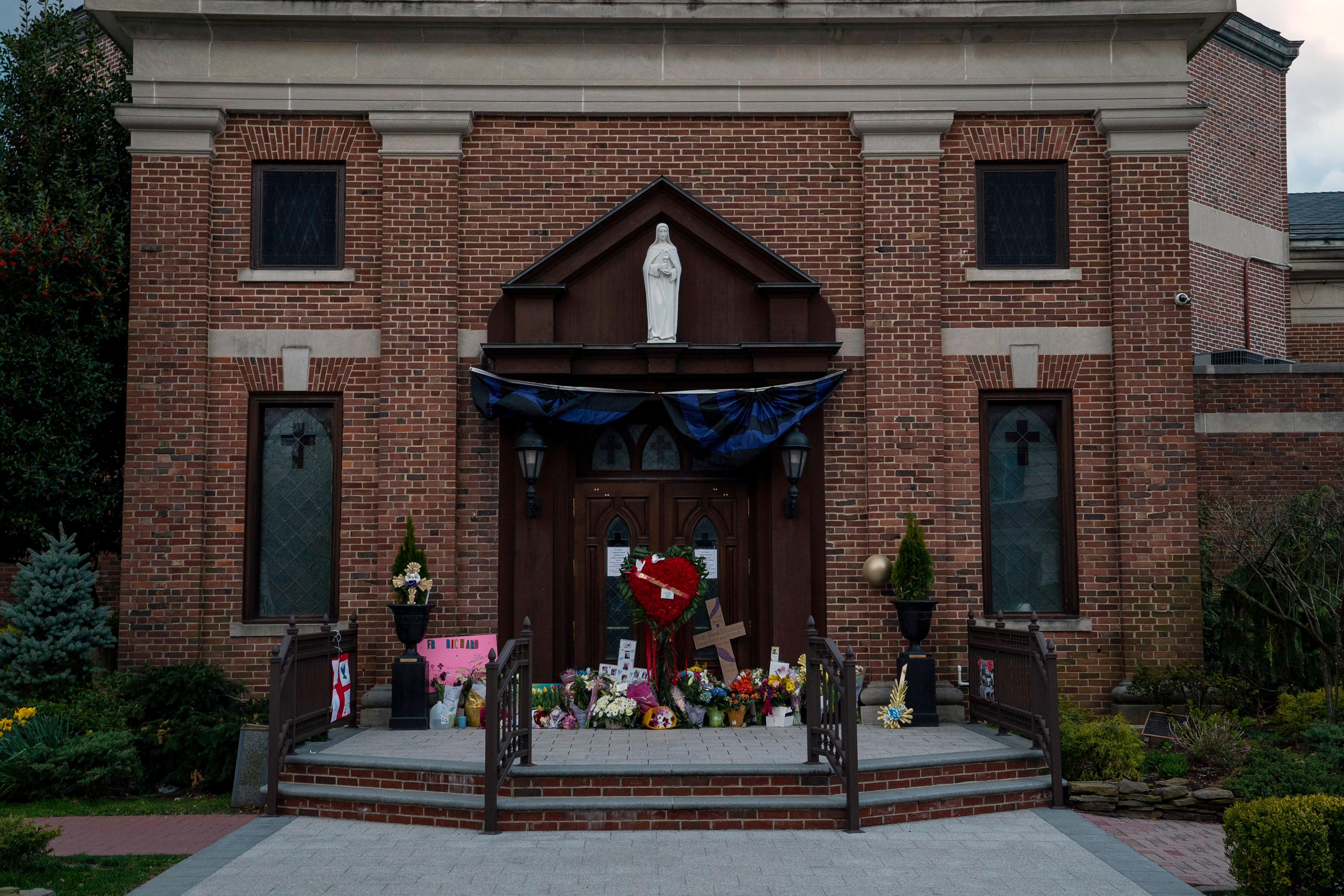 A memorial for Monsignor Richard Guastella, who died from Covid-19 on Thursday,  outside the doors of St. Clare Catholic Church in Staten Island, N.Y., on April 10, 2020.
