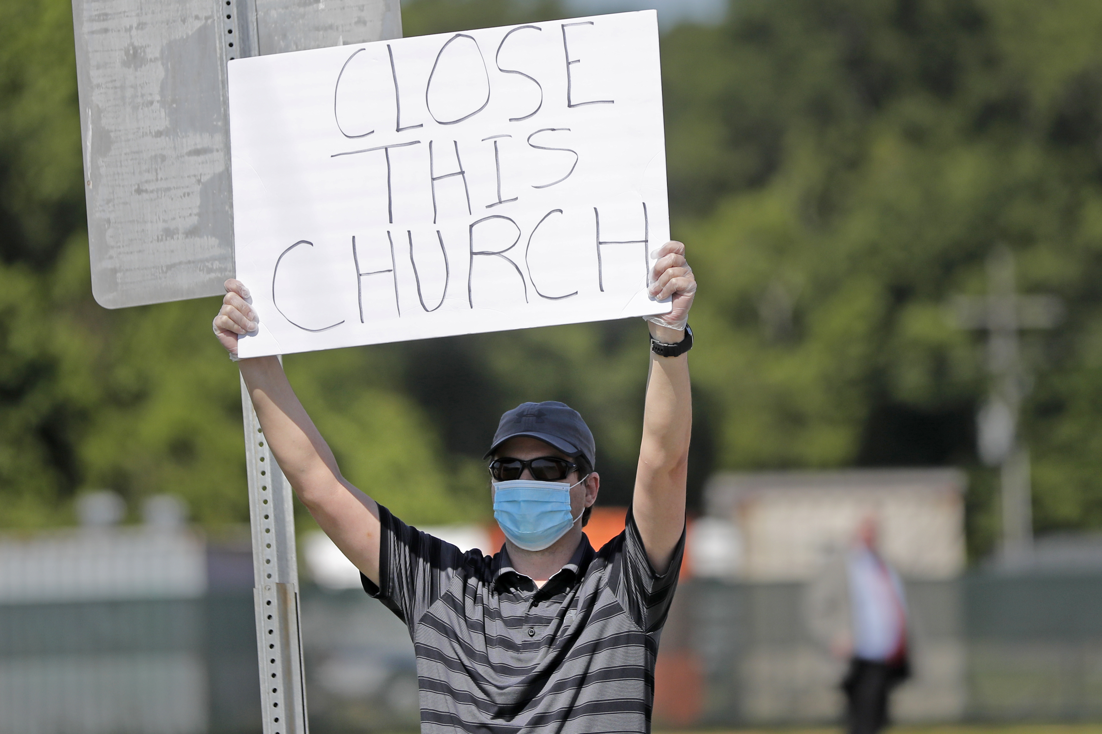 Protestor Trey Bennett holds a sign outside the East Baton Rouge Parish while waiting for  Pastor Tony Spell to post bond in Baton Rouge, La. on April 21, 2020.