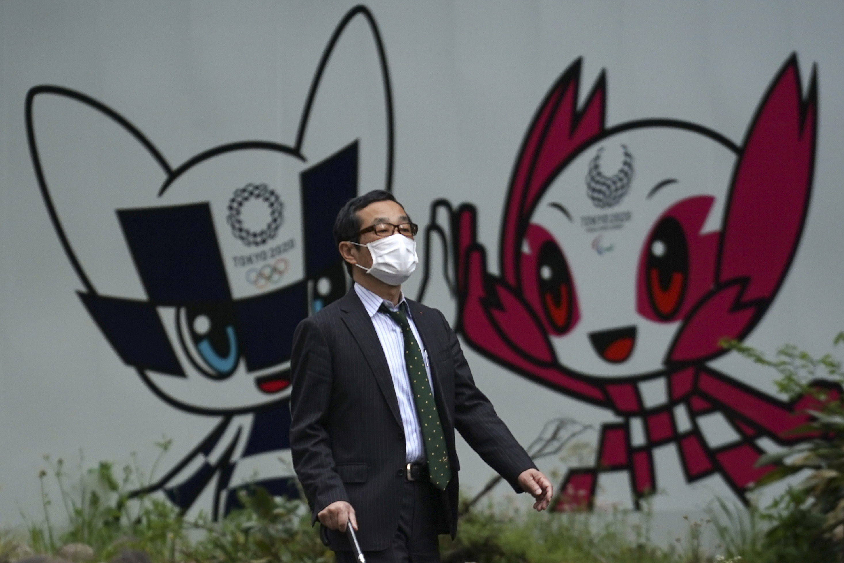 A man with a face mask against the spread of the new coronavirus walks in front of Miraitowa and Someity, mascots for the Tokyo 2020 Olympics and Paralympics at a park in Tokyo Tuesday, April 28, 2020. Japan's Prime Minister Shinzo Abe expanded a state of emergency to all of Japan from just Tokyo and other urban areas as the virus continues to spread.