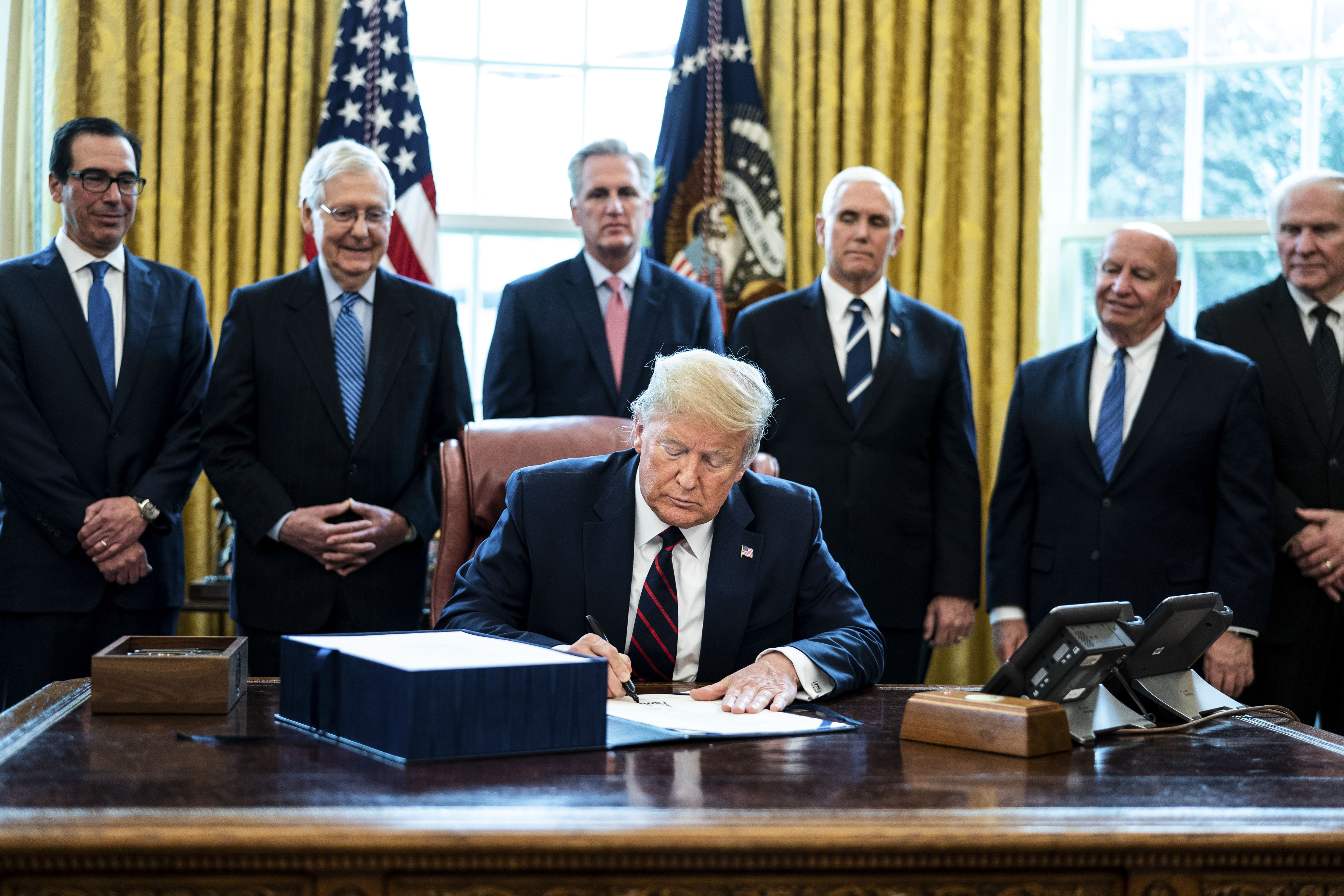President Donald Trump signs the Coronavirus Aid, Relief, and Economic Security (CARES) Act, in the Oval Office of the White House in Washington, D.C., on Friday, March 27, 2020.