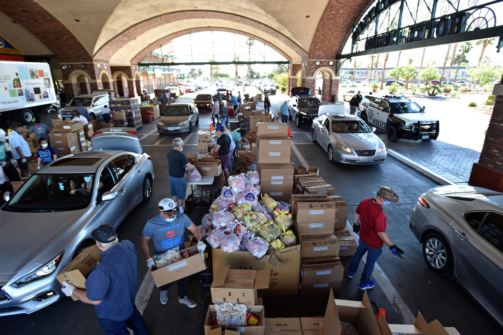Volunteers give out groceries at a drive-thru Three Square Food Bank emergency food distribution site at Boulder Station Hotel & Casino in response to an increase in demand amid the coronavirus pandemic on April 29, 2020 in Las Vegas, Nevada.