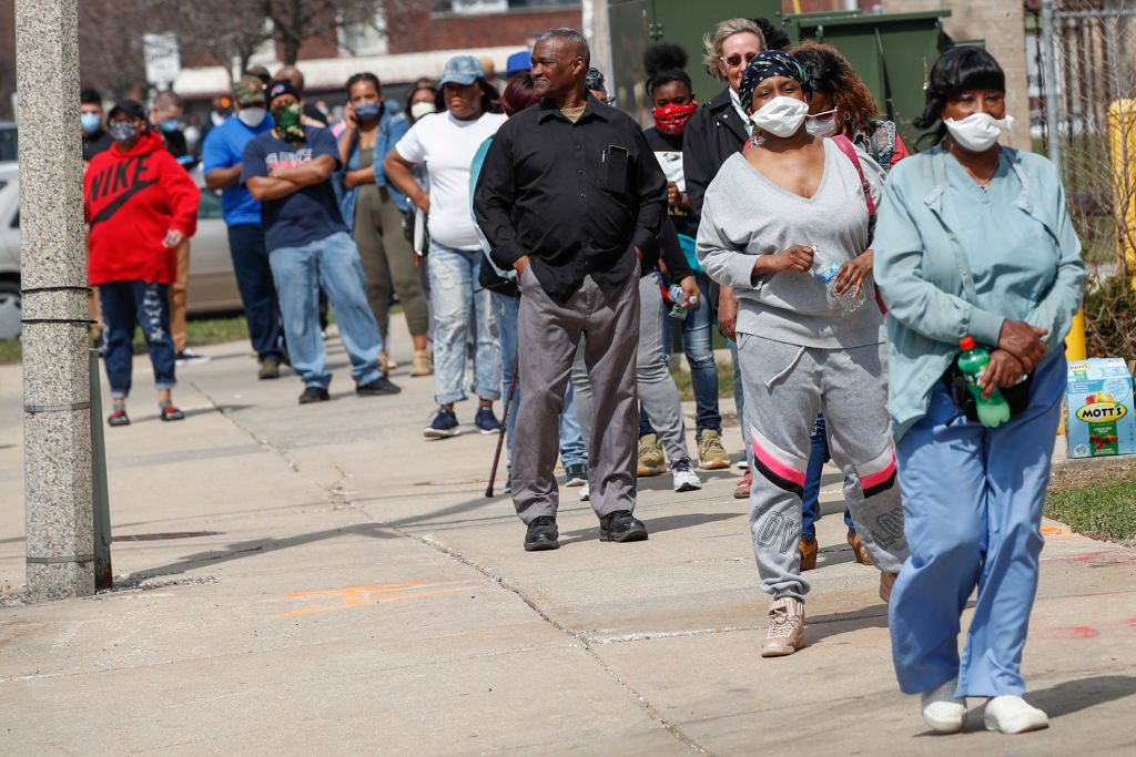 Residents wait in long line to vote in a presidential primary election outside the Riverside High School in Milwaukee, Wisconsin, on April 7, 2020.