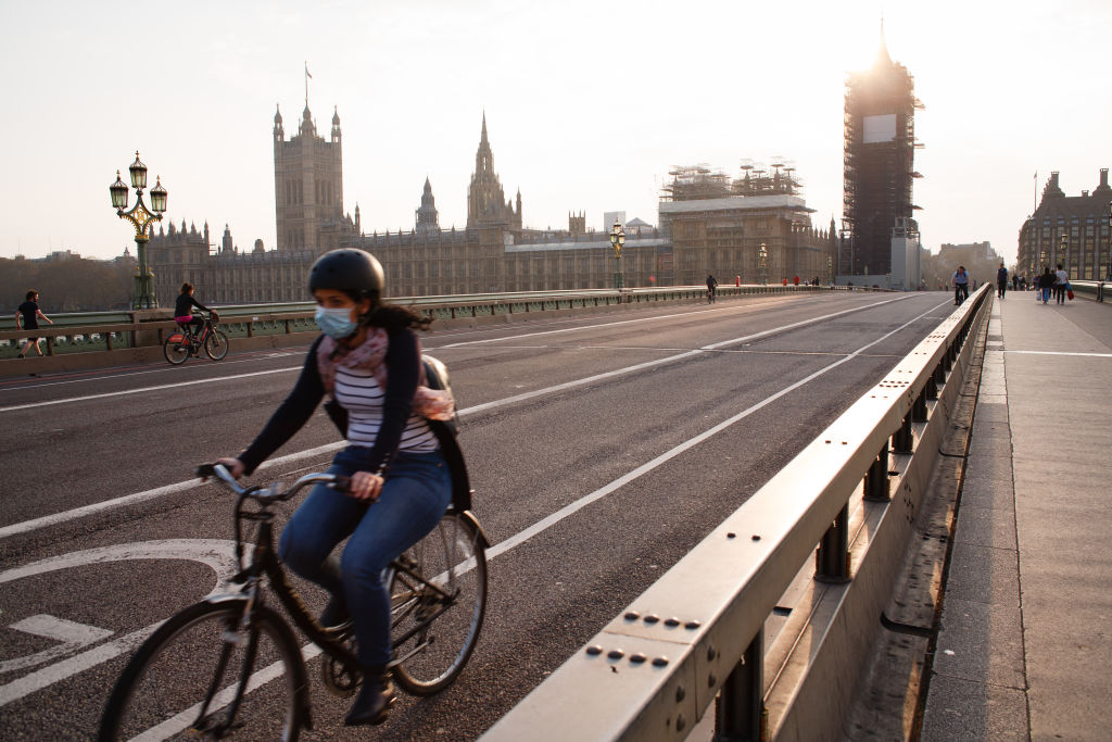 A cyclist wearing a face mask rides across a near-deserted Westminster Bridge in London, England, on April 8, 2020.
