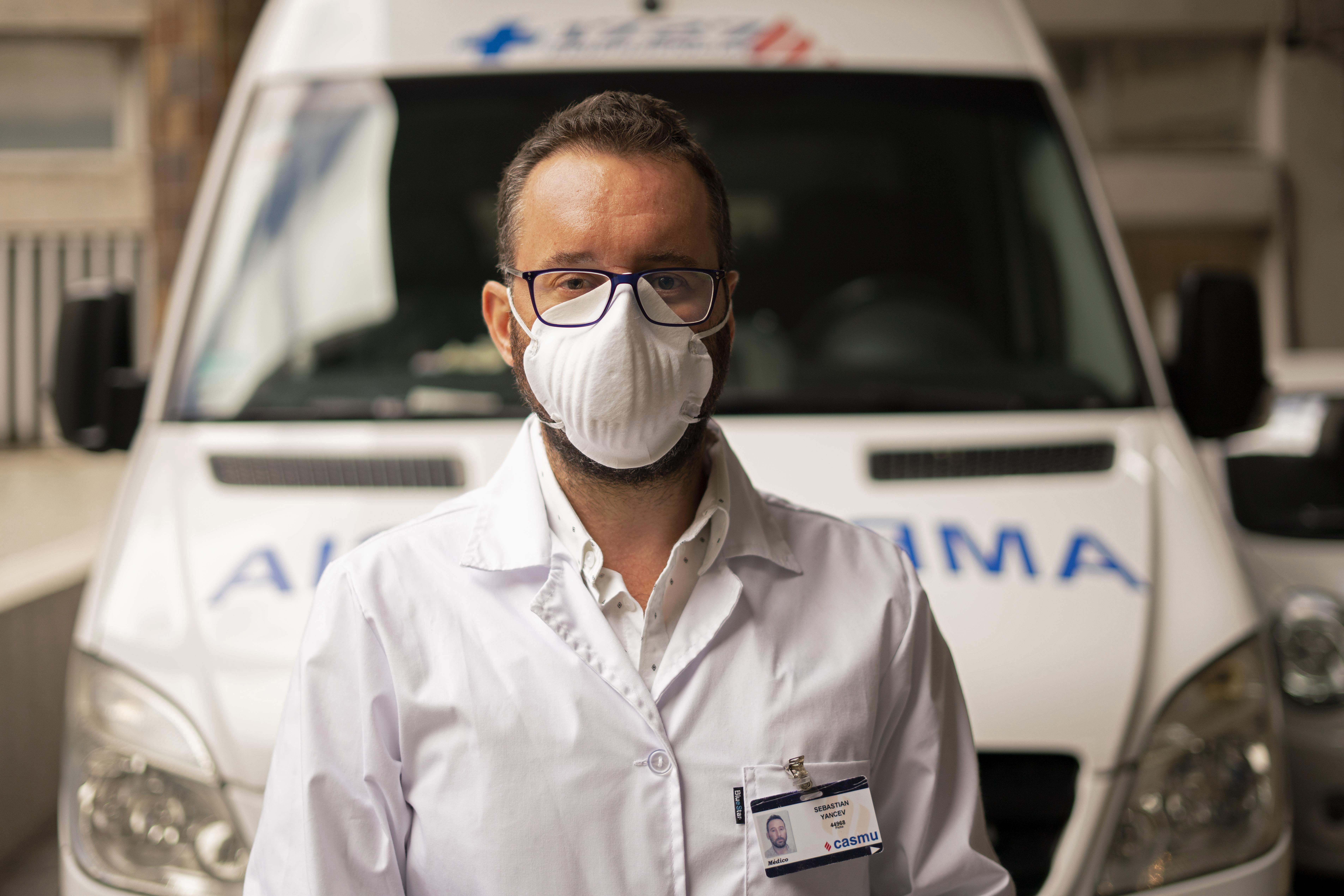 Doctor Sebastian Yancev, who helped diagnose the new coronavirus onboard the Australian Greg Mortimer cruise, stands in front of the ambulance that was used to move patients to local hospitals in Montevideo, Uruguay, on April 7, 2020.
